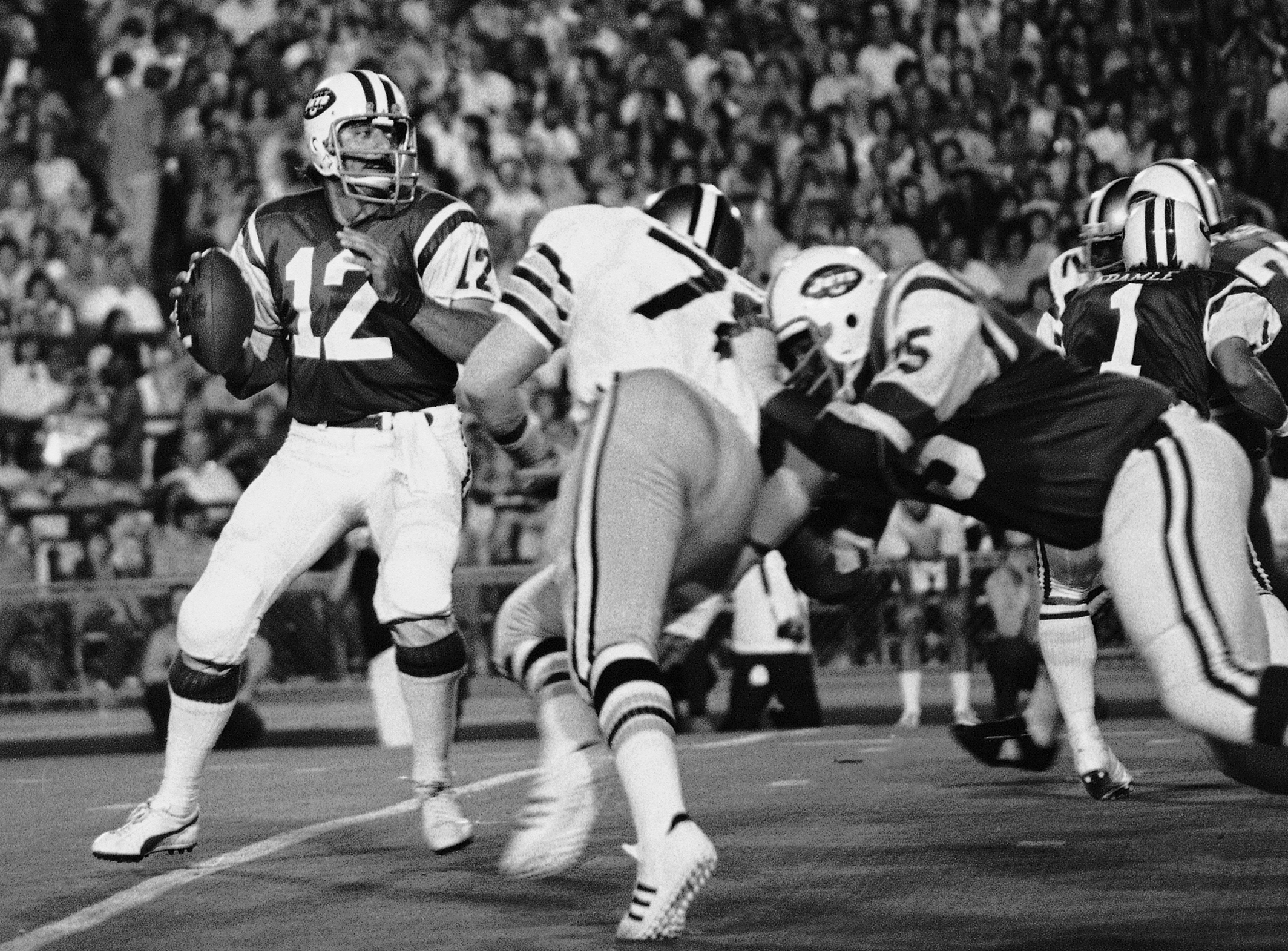 FILE- In this Sept. 2, 1973, file photo, New York Jets' Joe Namath (12) gets set to launch a delivery to Rick Caster as New Orleans Saints Billy Newsome (78) puts on the pressure and Jets' Winston Hill (75) blocks. Hill, a durable Pro Bowl offensive tackl