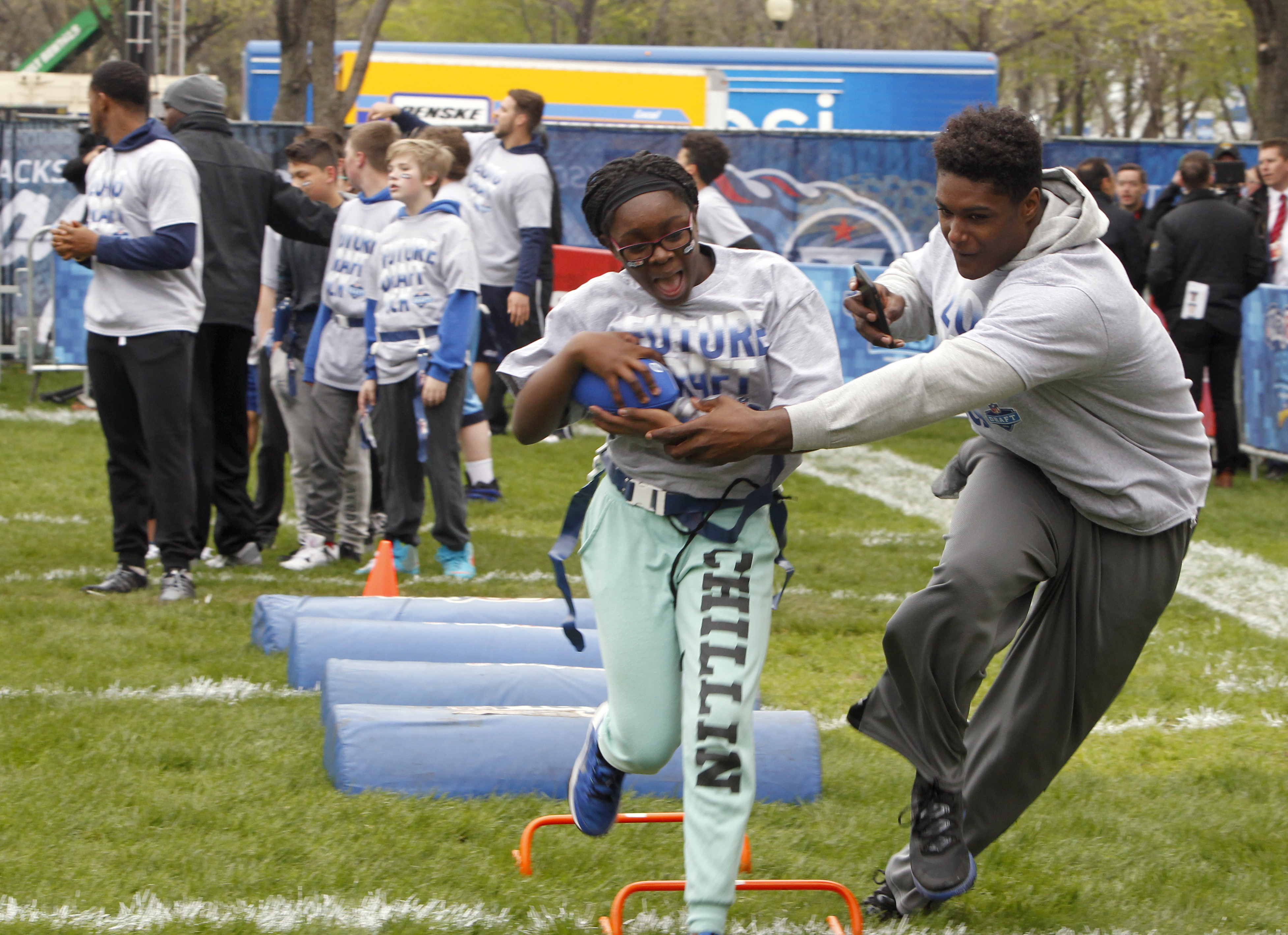 UCLA's Myles Jack, right, runs a drill with children during an NFL Play 60 event at Grant Park, Wednesday, April 27, 2016, in Chicago before Thursday's first round of the NFL football draft. (AP Photo/Kiichiro Sato)