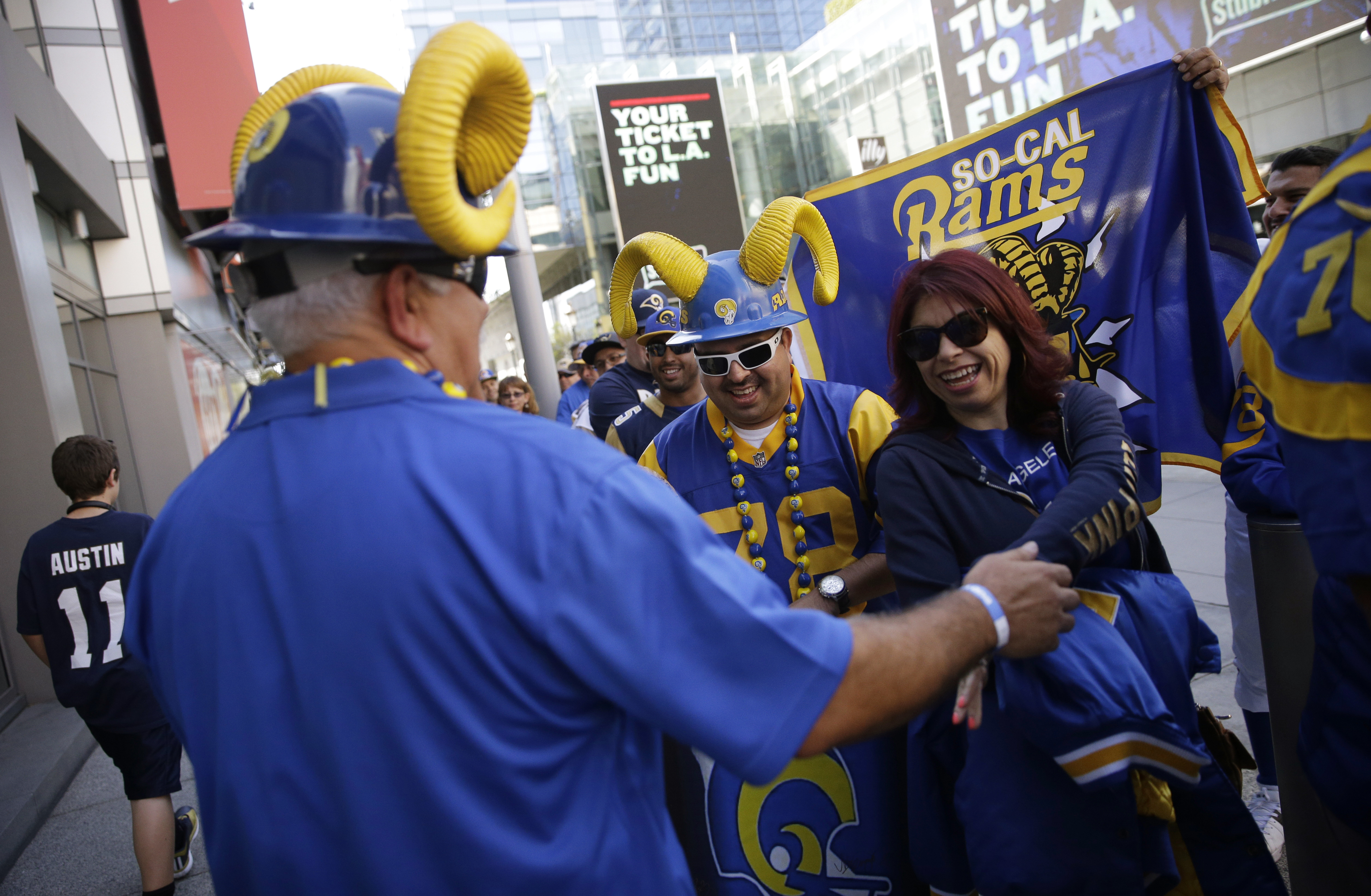 Los Angeles Rams fans greet each other while waiting in line to attend a  2016 NFL football draft party Thursday, April 28, 2016 in Los Angeles. (AP Photo/Jae C. Hong)