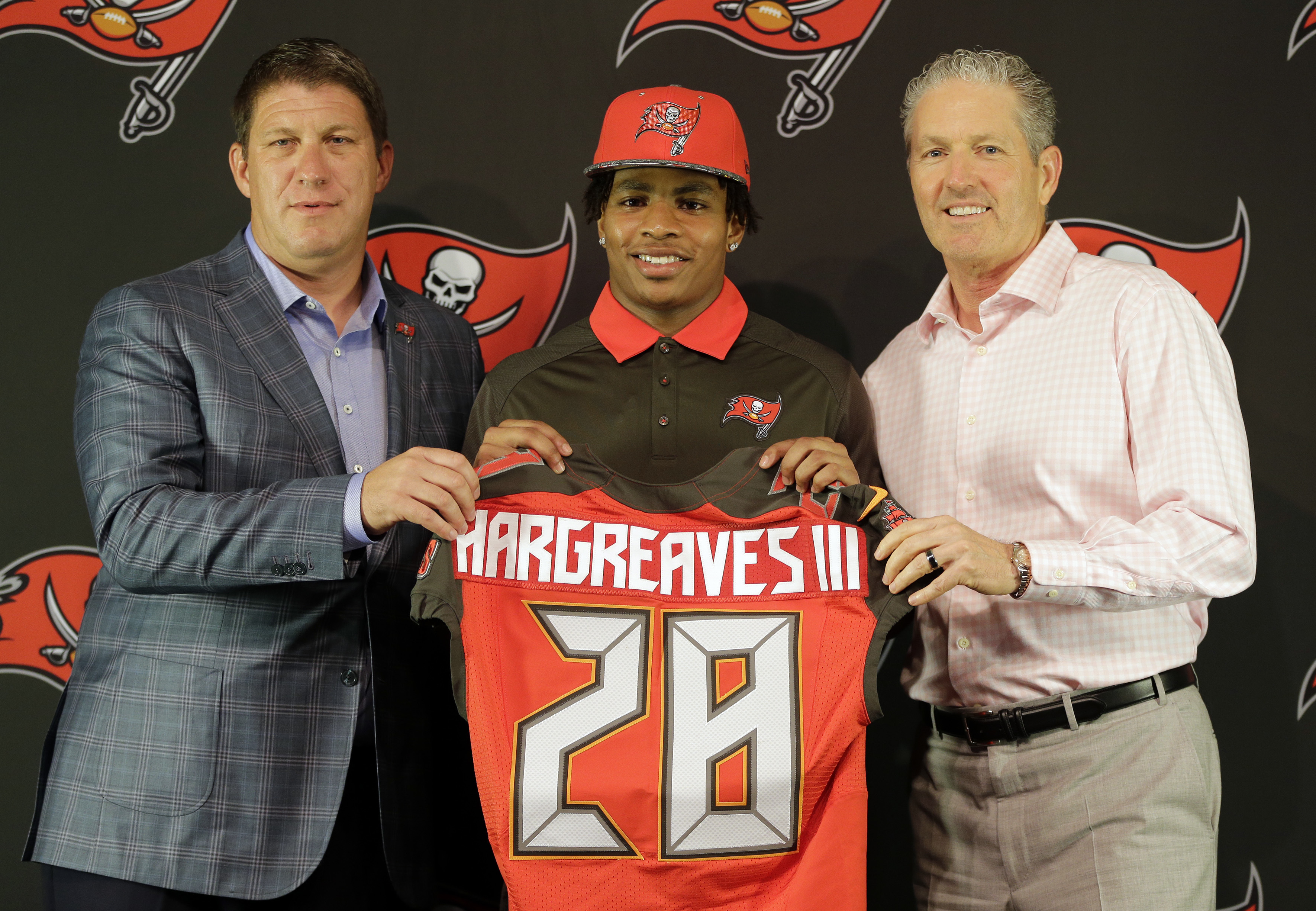 Tampa Bay Buccaneers first-round draft pick Vernon Hargreaves, center, poses with general manager Jason Licht, left, and head coach Dirk Koetter, right, during a news conference Friday, April 29, 2016, in Tampa, Fla. Hargreaves, formally of the University