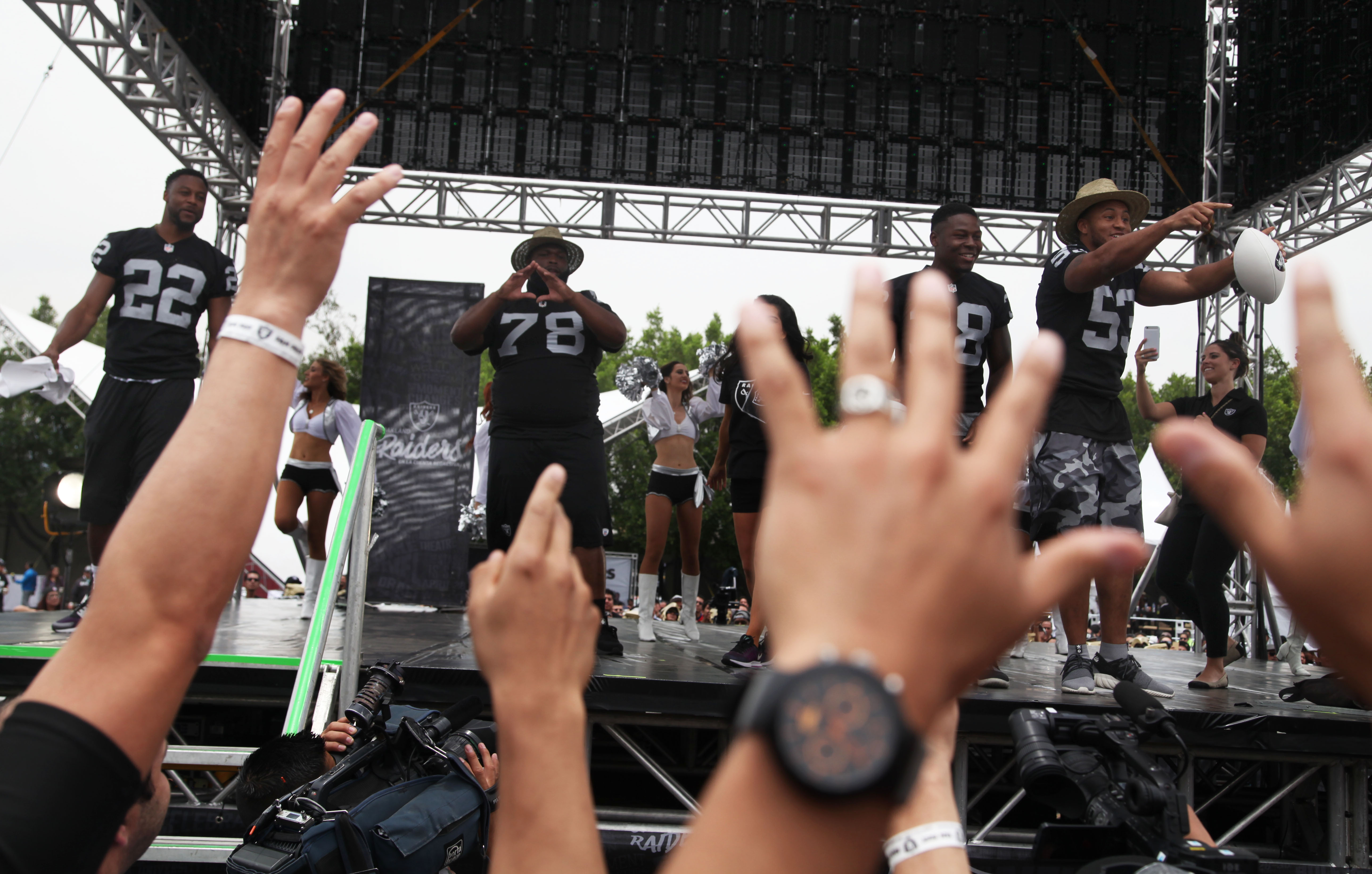 Oakland Raiders players, from left, Taiwan Jones (22), Justin Ellis (78), T.J. Carrie (38) and Malcolm Smith (53) dance before fans at Azteca Stadium where the team announced their third day NFL picks in Mexico City, Saturday, April 30, 2016. The Raiders