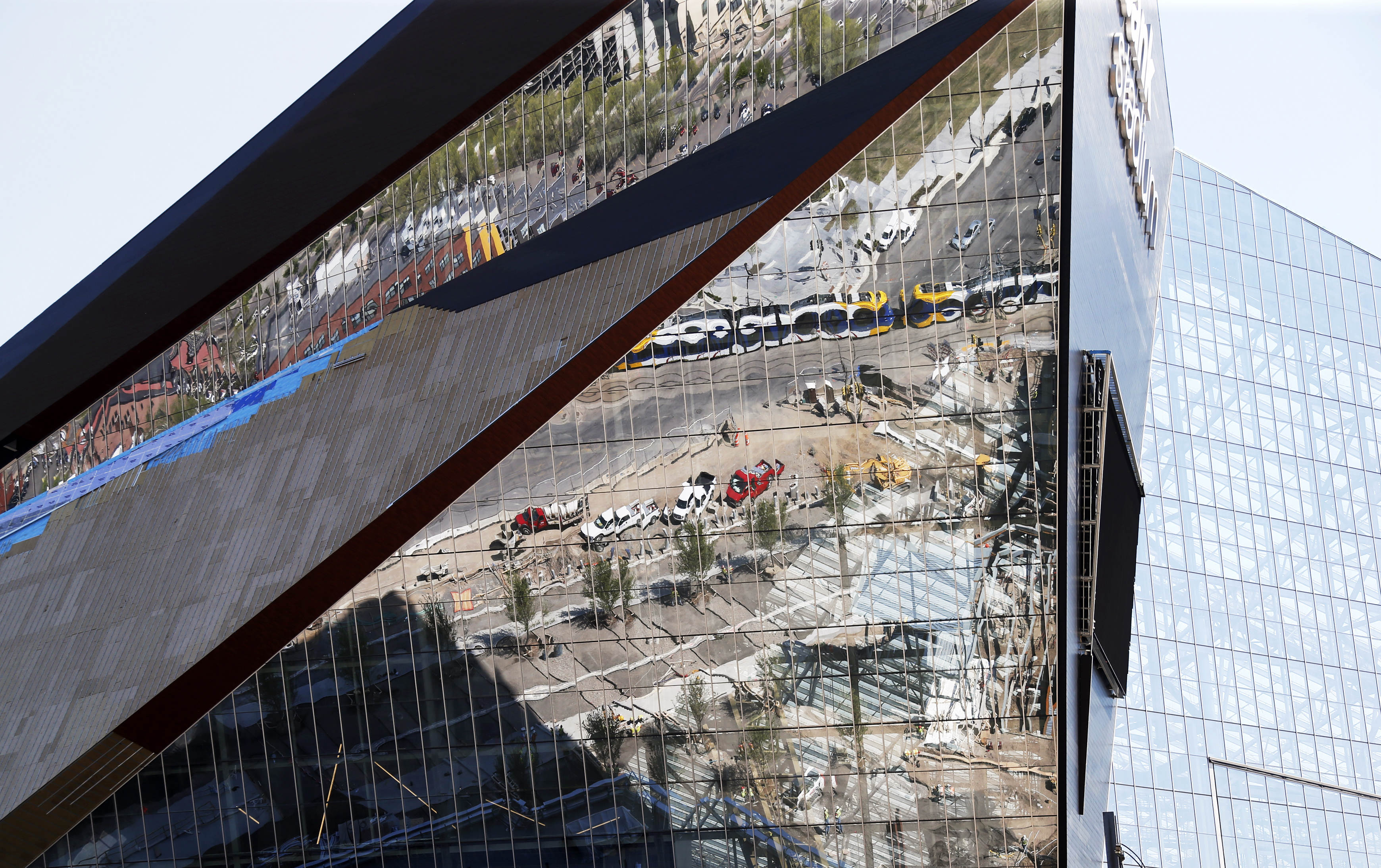 Newly planted trees and a light rail train are reflected in the facade of the new $1.2 billion U.S. Bank Stadium, the new stadium for the home to the Minnesota Vikings NFL football team, Wednesday, May 5, 2016, in Minneapolis. (AP Photo/Jim Mone)