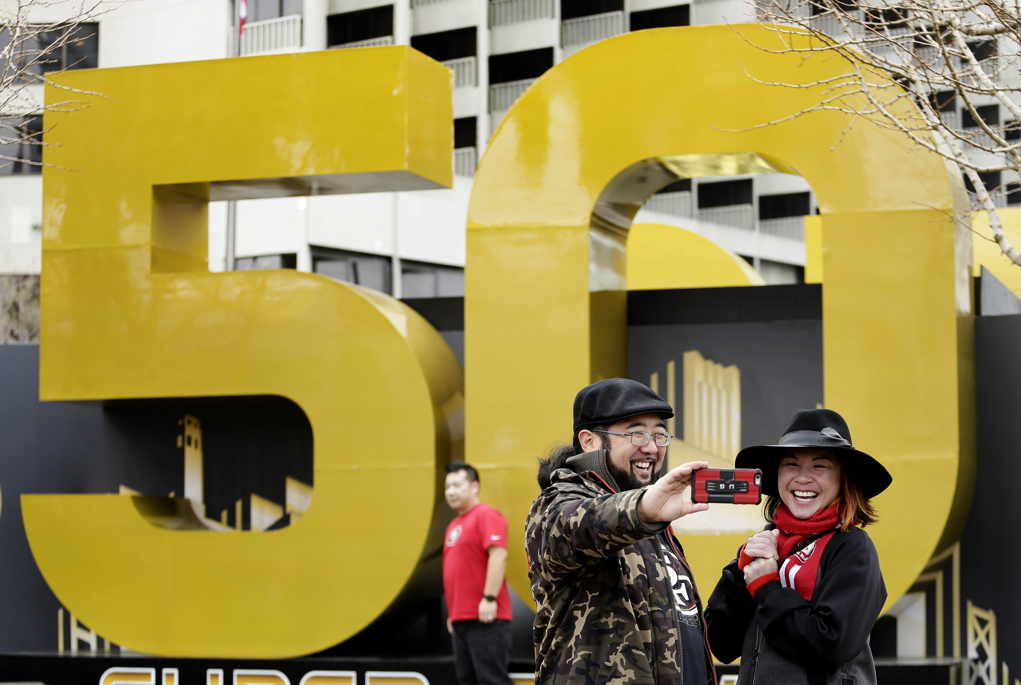 FILE - In this Feb. 3, 2016 file photo, Carissa Lou and Marc Shimamoto pose for a selfie in front of a Super Bowl 50 sign at Super Bowl City in San Francisco. San Francisco netted nearly $2 million from co-hosting the Super Bowl, with money coming largely