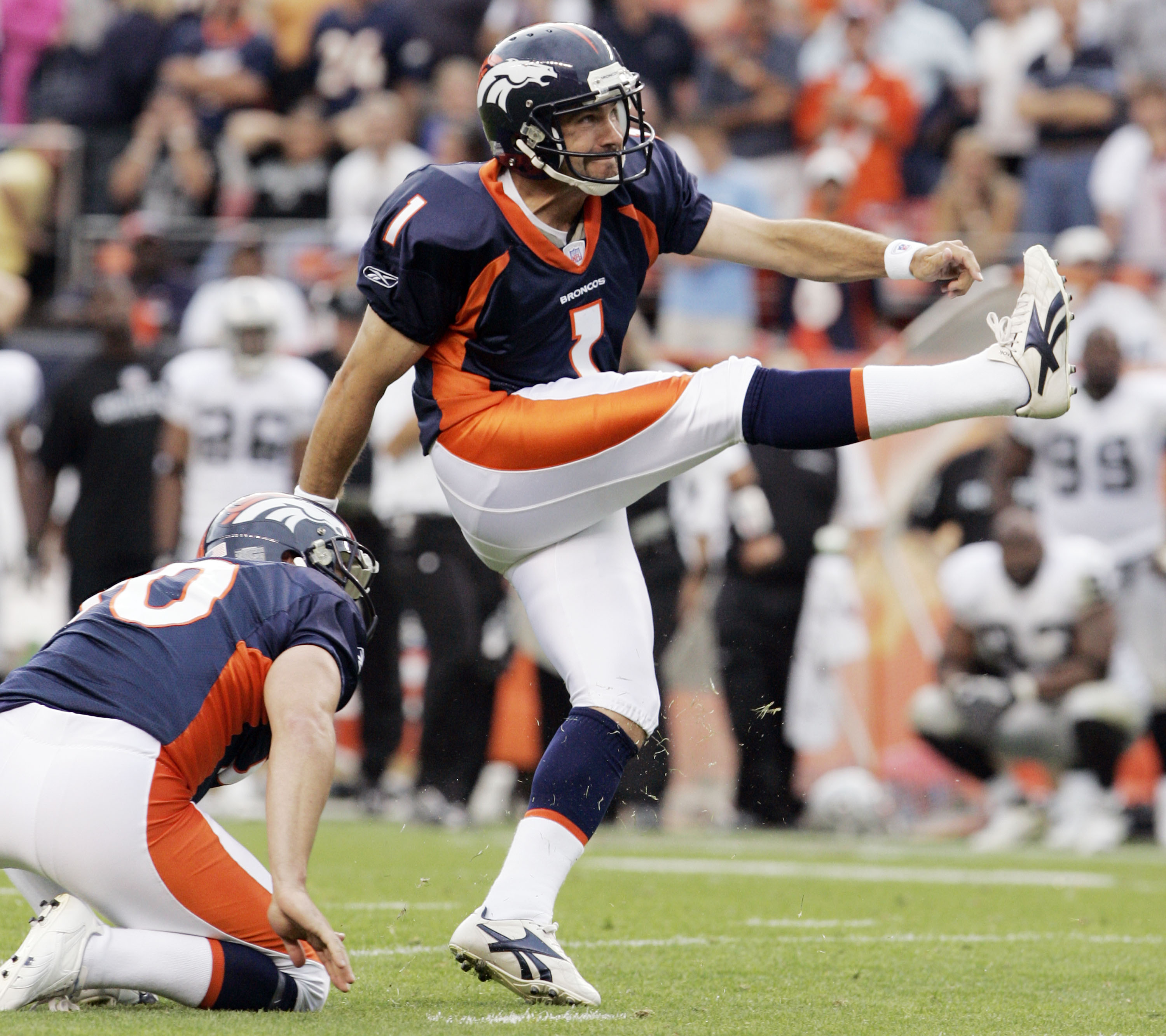 FILE - In this Sunday, Sept. 16, 2007 file photo, Denver Broncos kicker Jason Elam (1) follows through as he kicks the game-winning field goal in overtime against the Oakland Raiders during a football game in Denver. A trio of former players is heading in