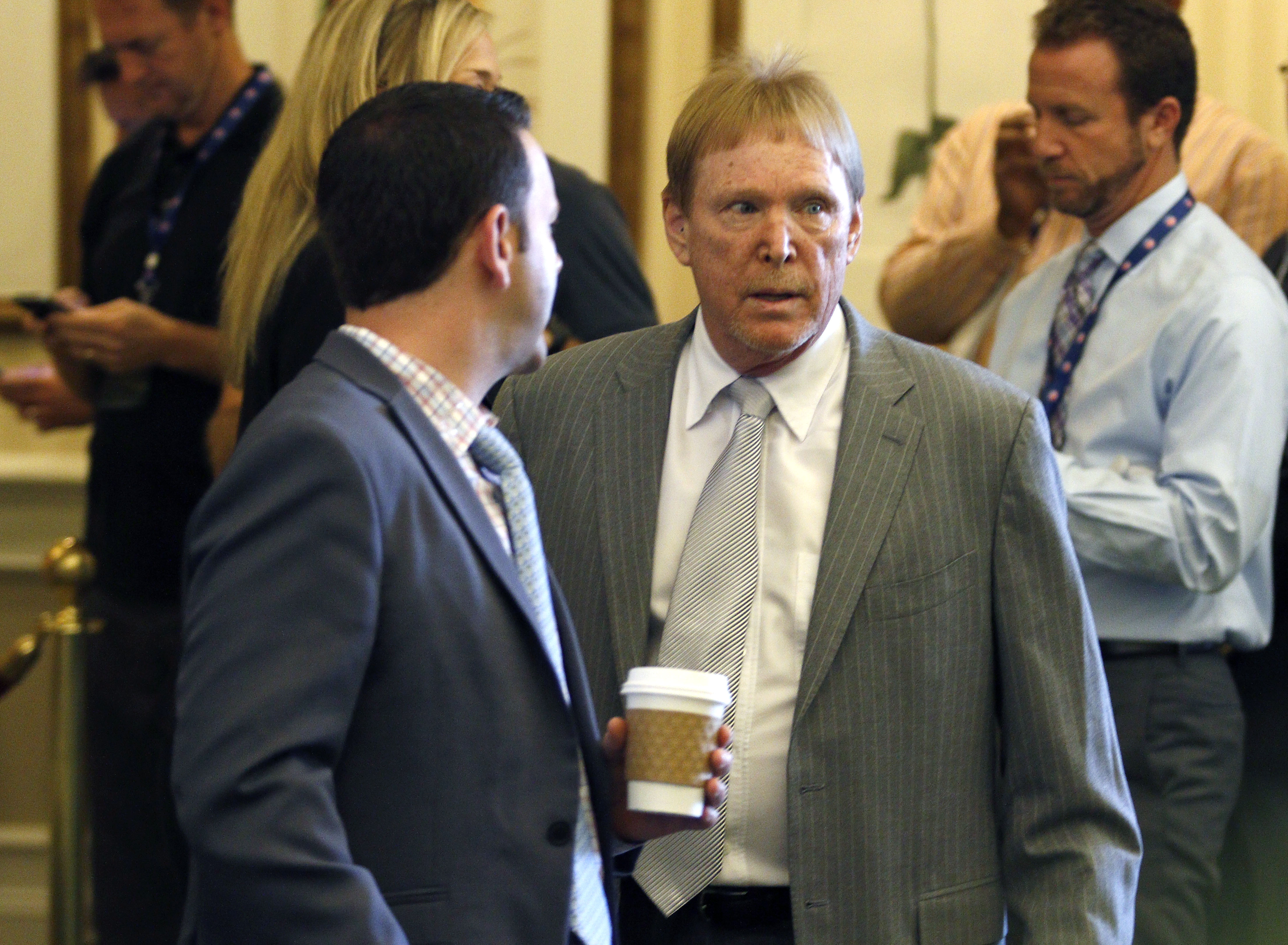 CORRECTS FIRST NAME TO MARK, NOT MIKE - Oakland Raiders owner Mark Davis, right,  makes his way into the NFL owner's meeting in Charlotte N.C., Tuesday, May 24, 2016. (AP Photo/Bob Leverone)