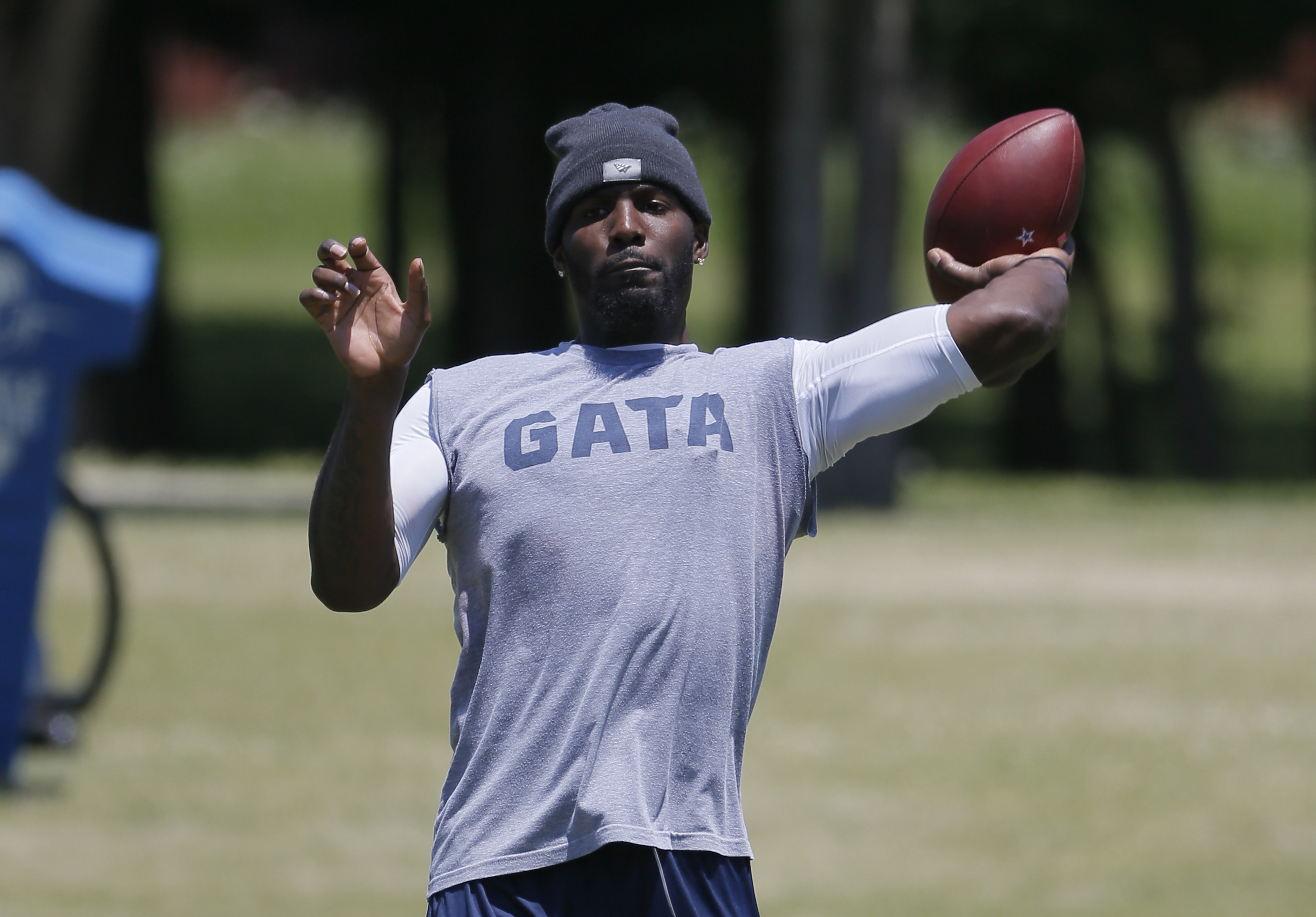 FILE - In this May 7, 2016, file phoito, Dallas Cowboys wide receiver Dez Bryant tosses the ball as he watches rookies work out during the team's NFL football minicamp in Irving, Texas. Quarterback Tony Romo is practicing for the first time since before l