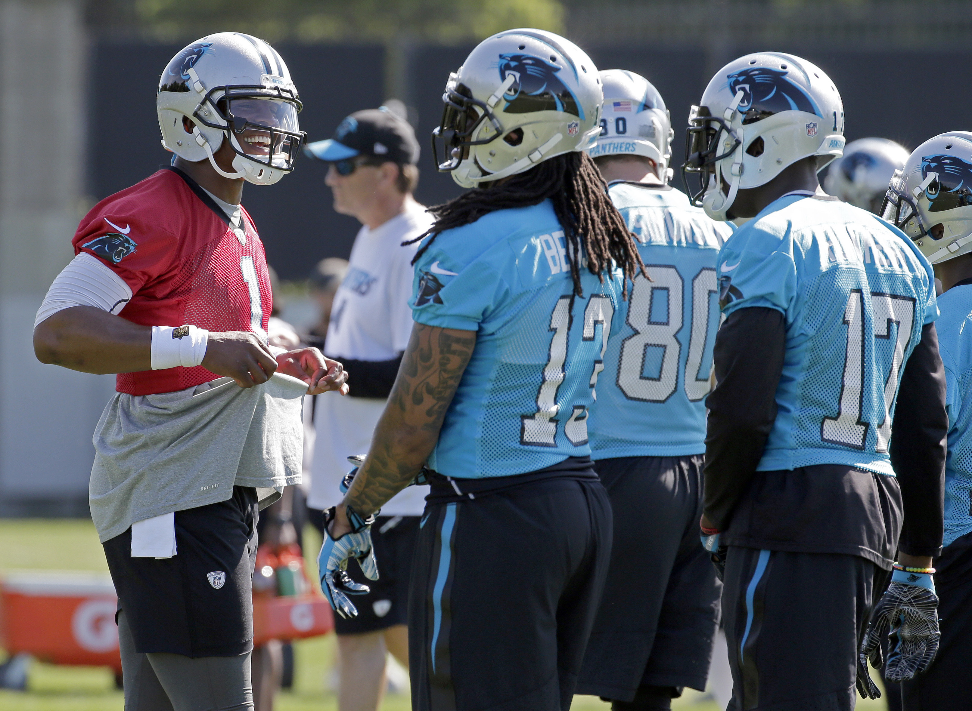 Carolina Panthers' Cam Newton, left, jokes with receivers Kelvin Benjamin, center, and Devin Funchess, right, during NFL football practice in Charlotte, N.C., Tuesday, May 31, 2016. (AP Photo/Chuck Burton)