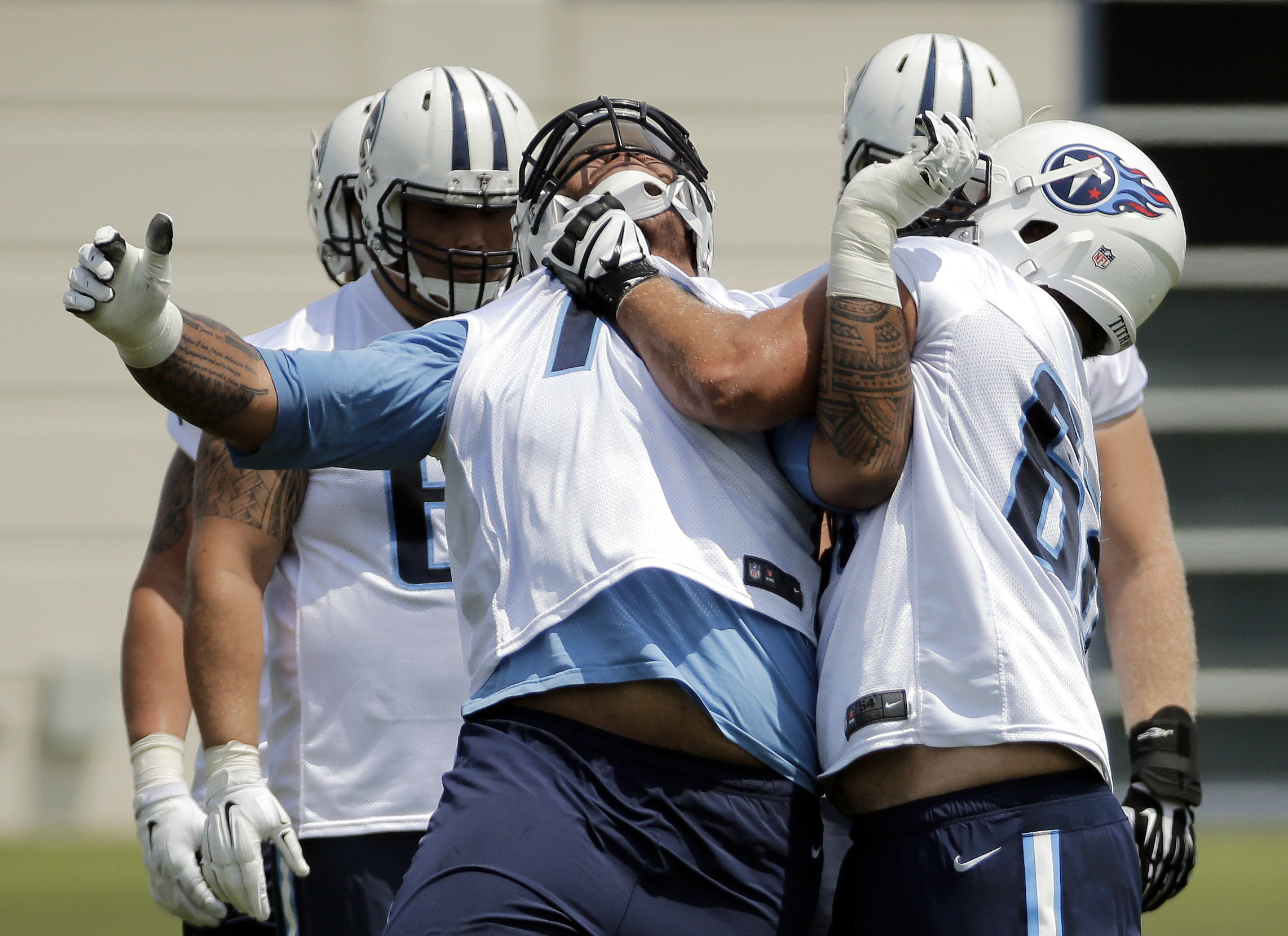 Tennessee Titans offensive linemen Tyler Marz, right, and Jeremiah Poutasi, center, run a drill during an NFL football practice, Wednesday, June 1, 2016, in Nashville, Tenn. (AP Photo/Mark Humphrey)