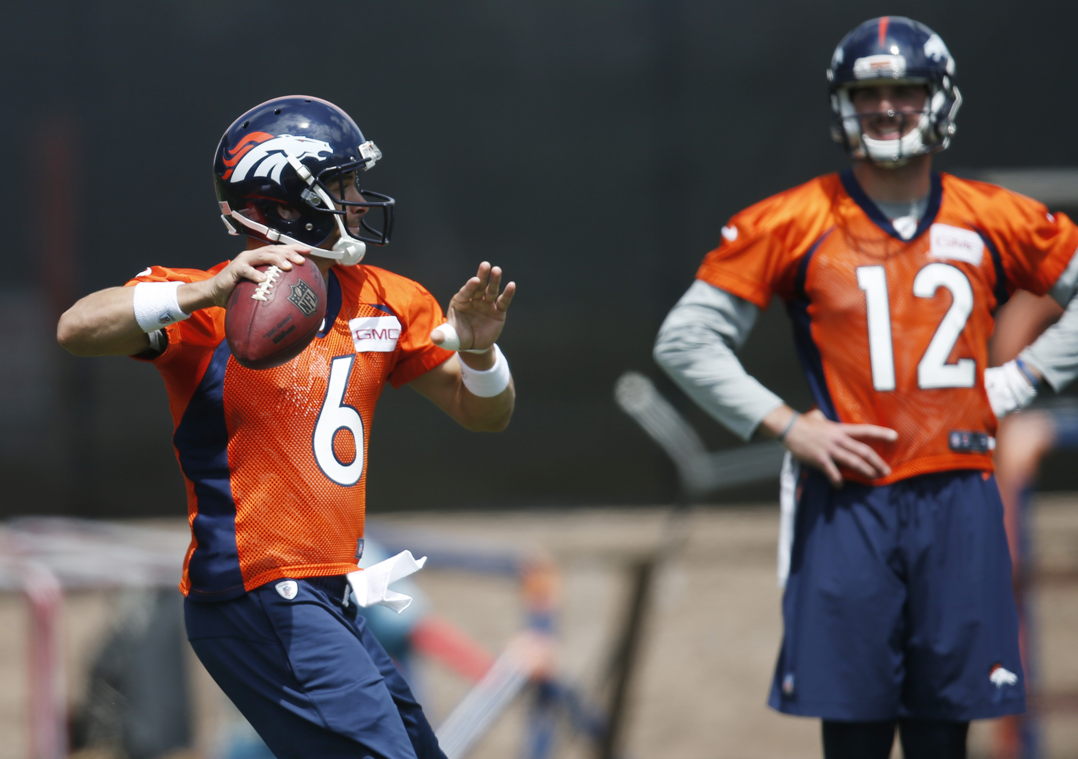 In this Tuesday, May 31, 2016, photograph, Denver Broncos quarterback Mark Sanchez, front, takes part in a passing drills as rookie quarterback Paxton Lynch looks on during an NFL football practice at the team's headquarters in Englewood, Colo. The Bronco