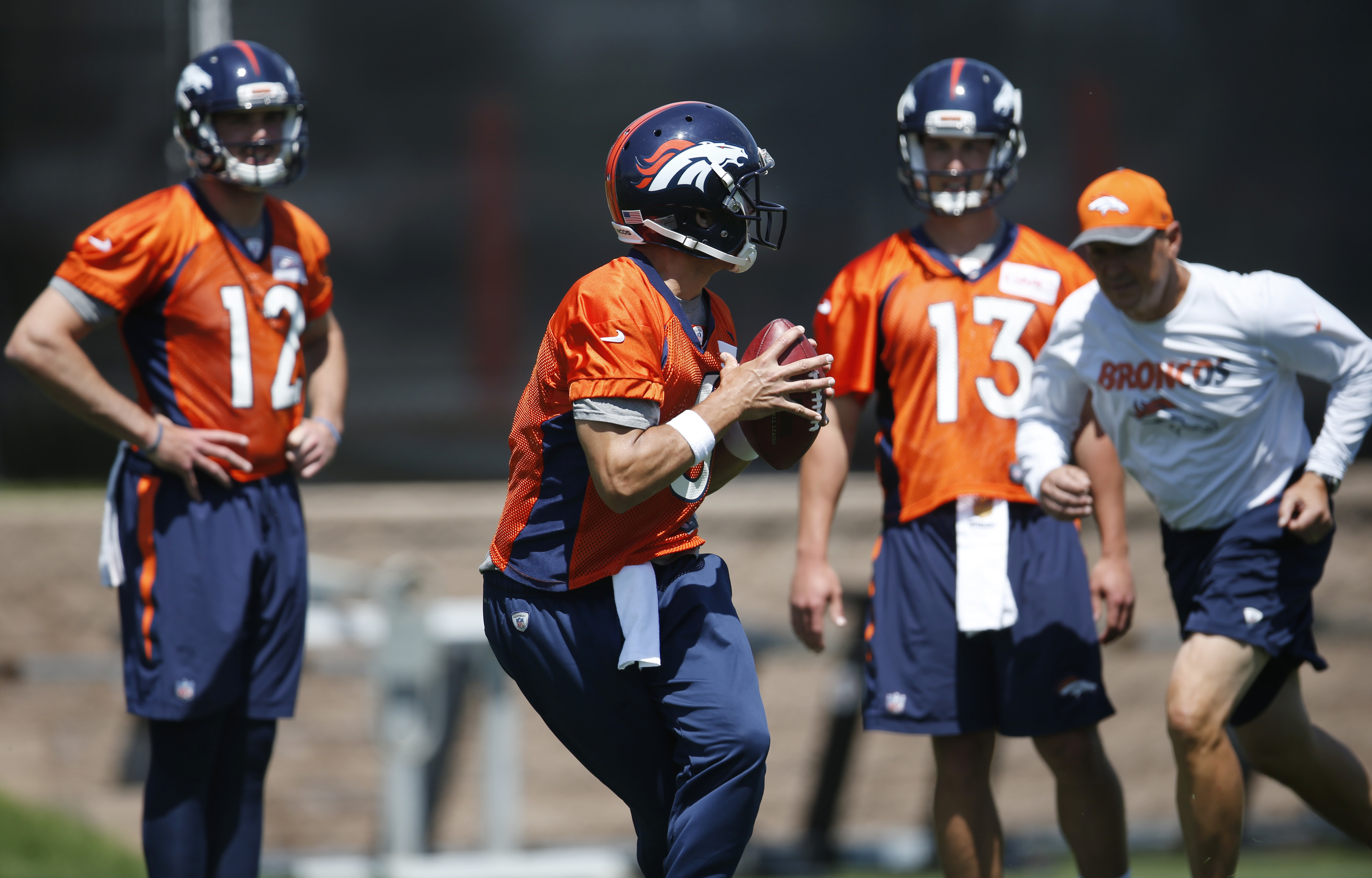 Denver Broncos quarterback Mark Sanchez, front, drops back to pass as, from back left, quarterbacks Paxton Lynch and Trevor Siemian and offensive coordinator Rick Dennison look on during an NFL football practice at the team's headquarters Tuesday, June 7,