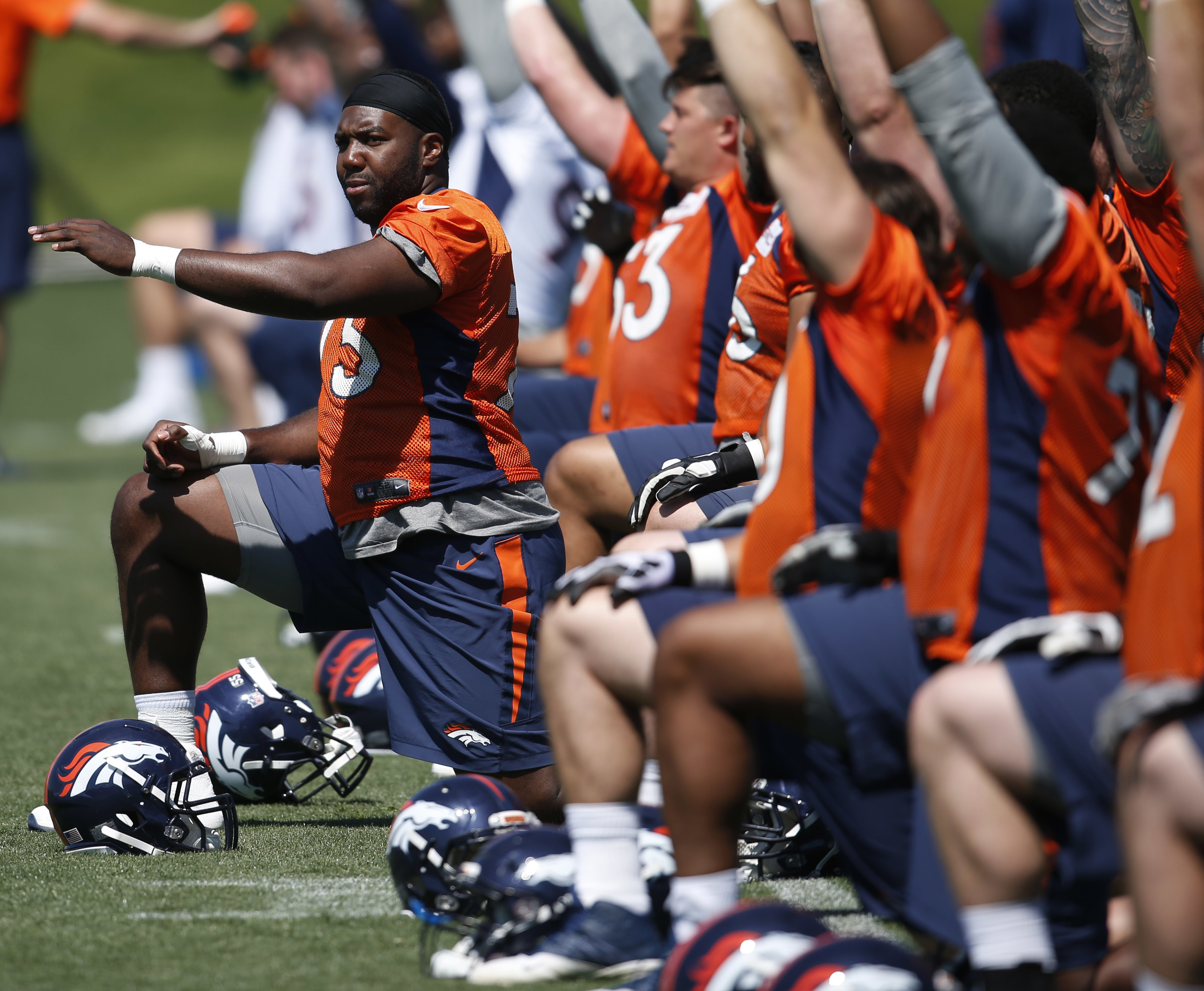 Denver Broncos tackle Russell Okung, left, stretches with teammates during an NFL football practice at the team's headquarters Wednesday, June 8, 2016, in Englewood, Colo. (AP Photo/David Zalubowski)