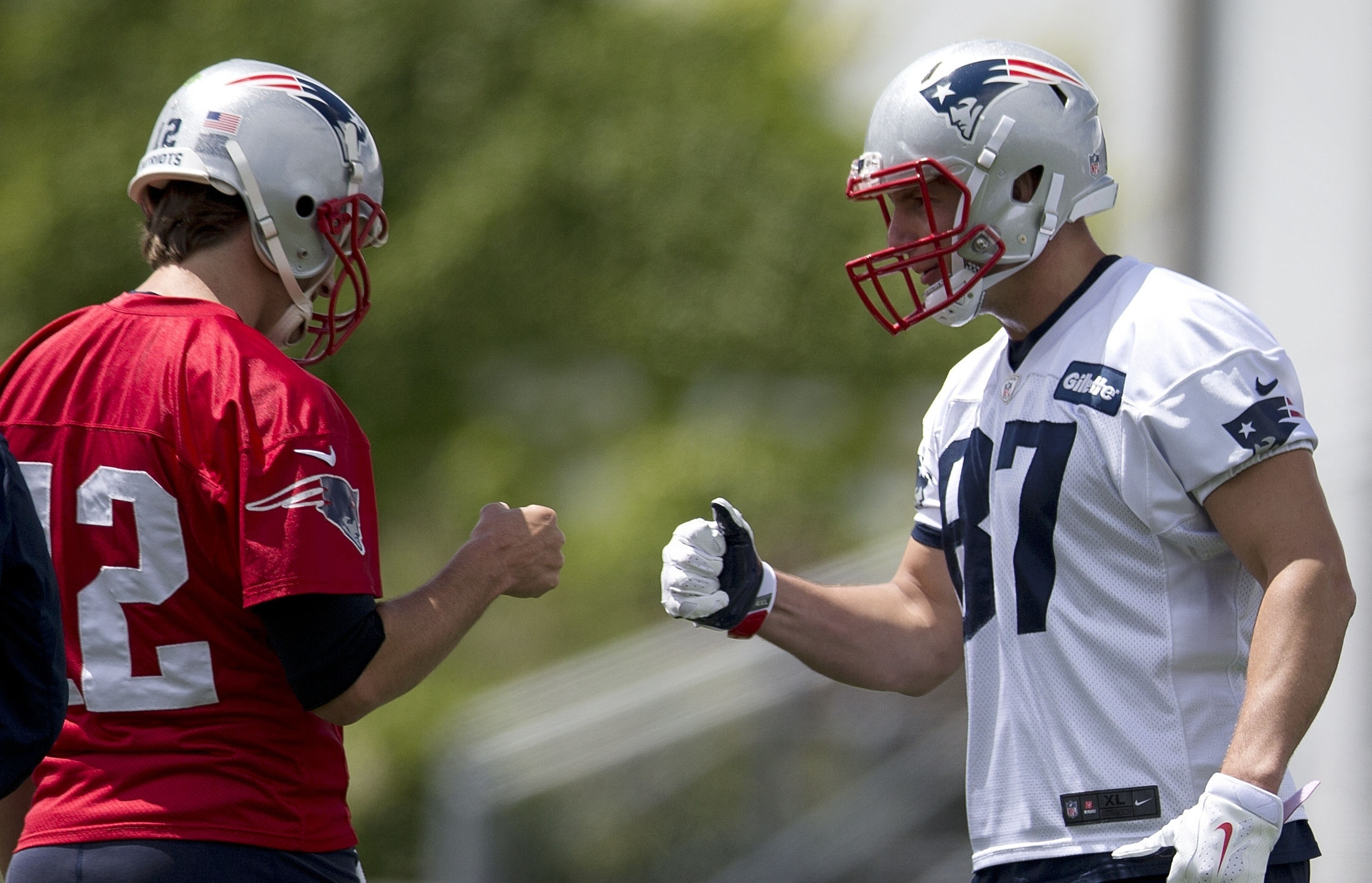 New England Patriots quarterback Tom Brady (12) bumps fists with tight end Rob Gronkowski (87) during an NFL football practice Monday, June 13, 2016, in Foxborough, Mass. (AP Photo/Michael Dwyer)
