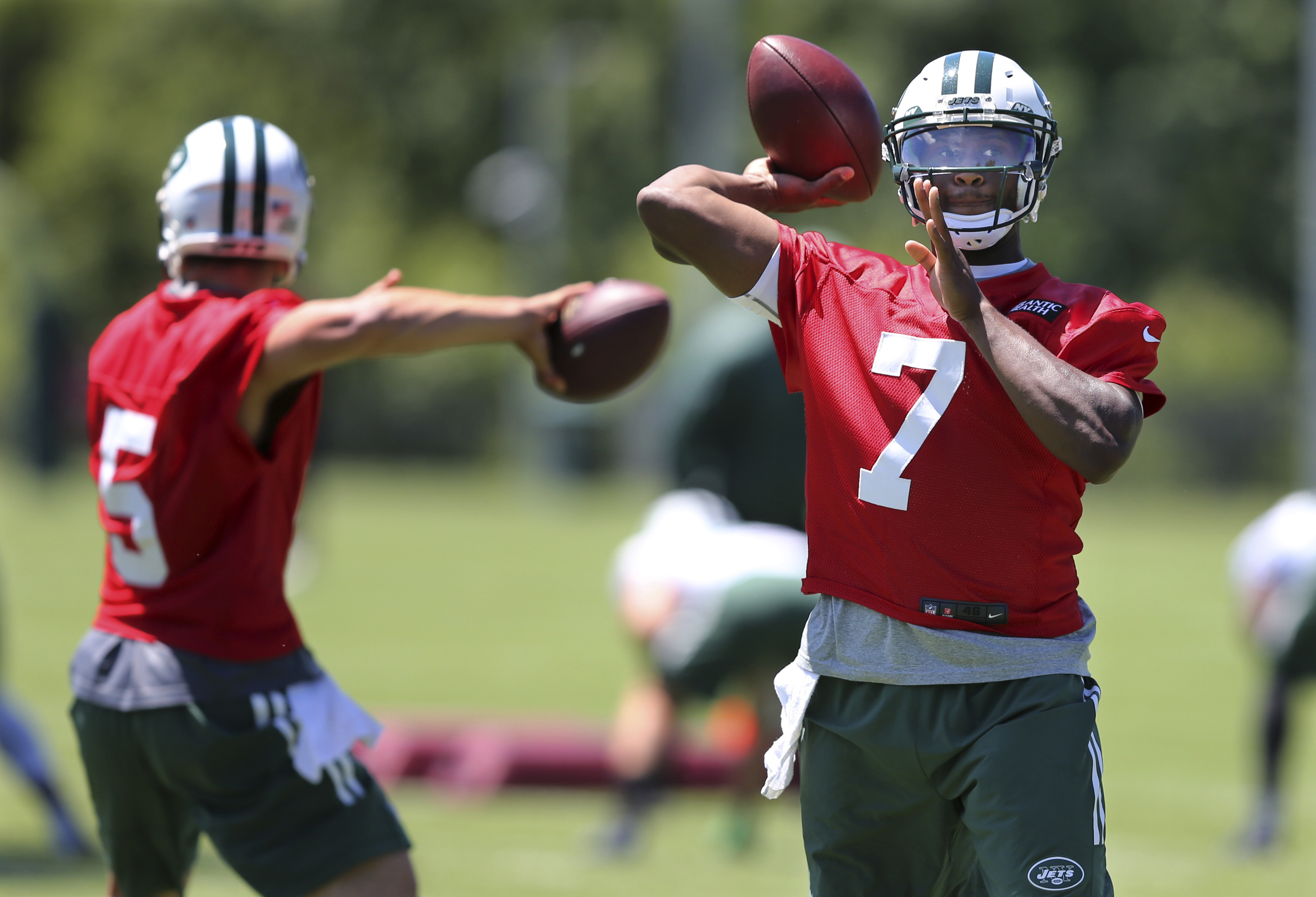 New York Jets quarterbacks Christian Hackenberg (5) and Geno Smith (7) throw passes during NFL football practice Tuesday, June 14, 2016, in Florham Park, N.J. (AP Photo/Mel Evans)