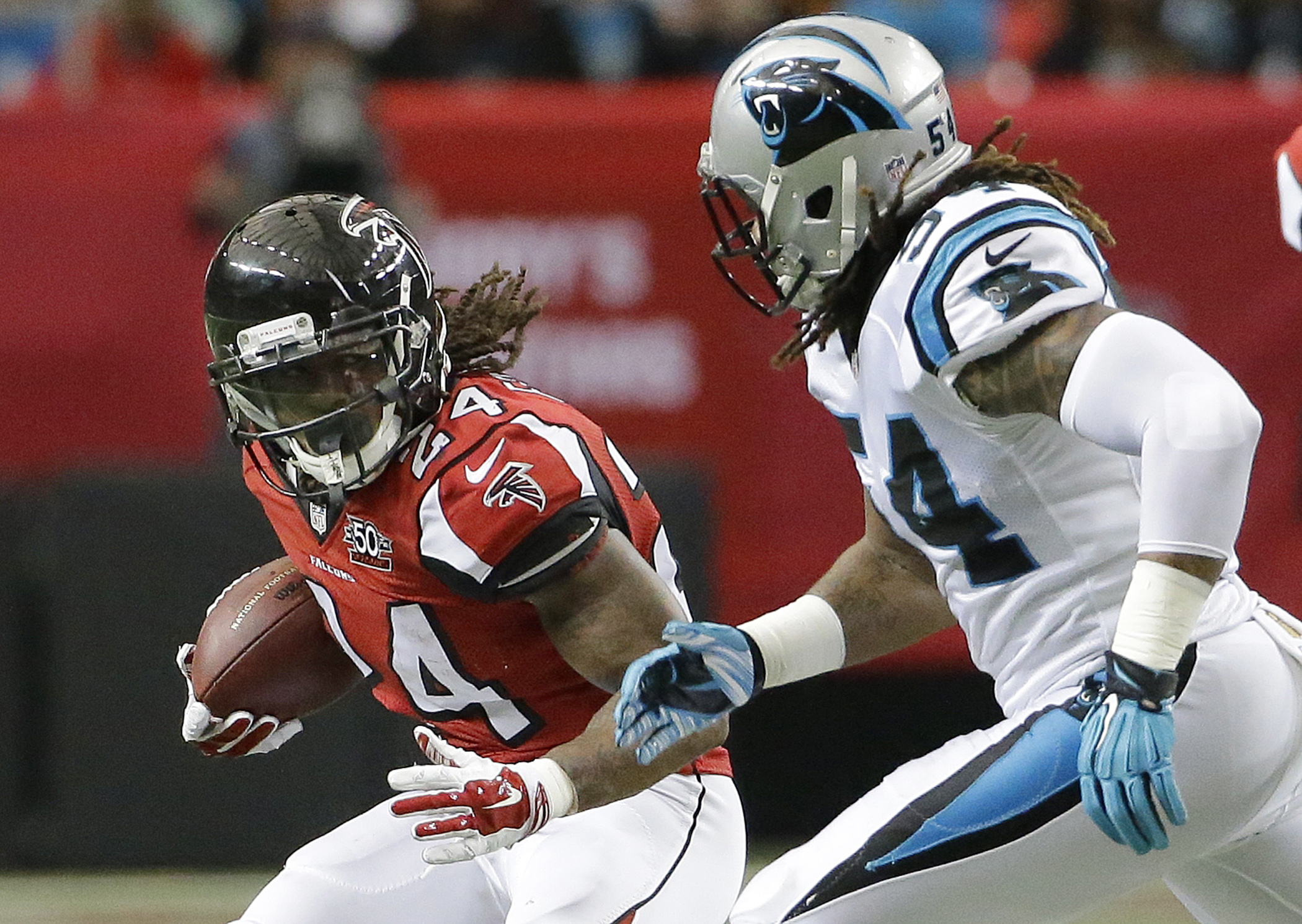 FILE - In this Sunday, Dec. 27, 2015 file photo, Atlanta Falcons running back Devonta Freeman (24) runs against Carolina Panthers outside linebacker Shaq Green-Thompson (54) during the first half of an NFL football game in Atlanta. Atlanta Falcons running