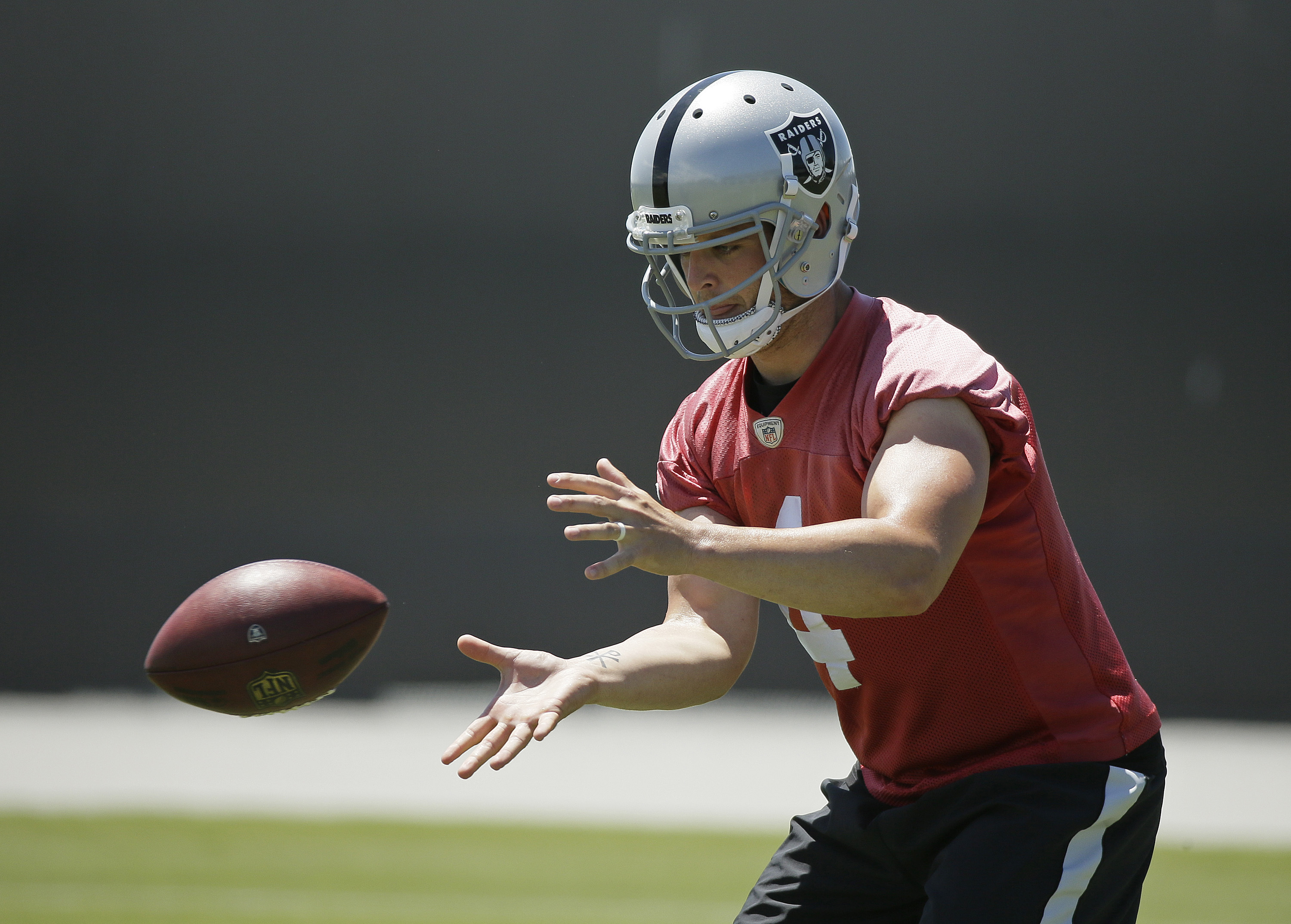 Oakland Raiders quarterback Derek Carr catches a snap during the team's NFL football minicamp Wednesday, June 15, 2016, in Alameda, Calif. (AP Photo/Eric Risberg)