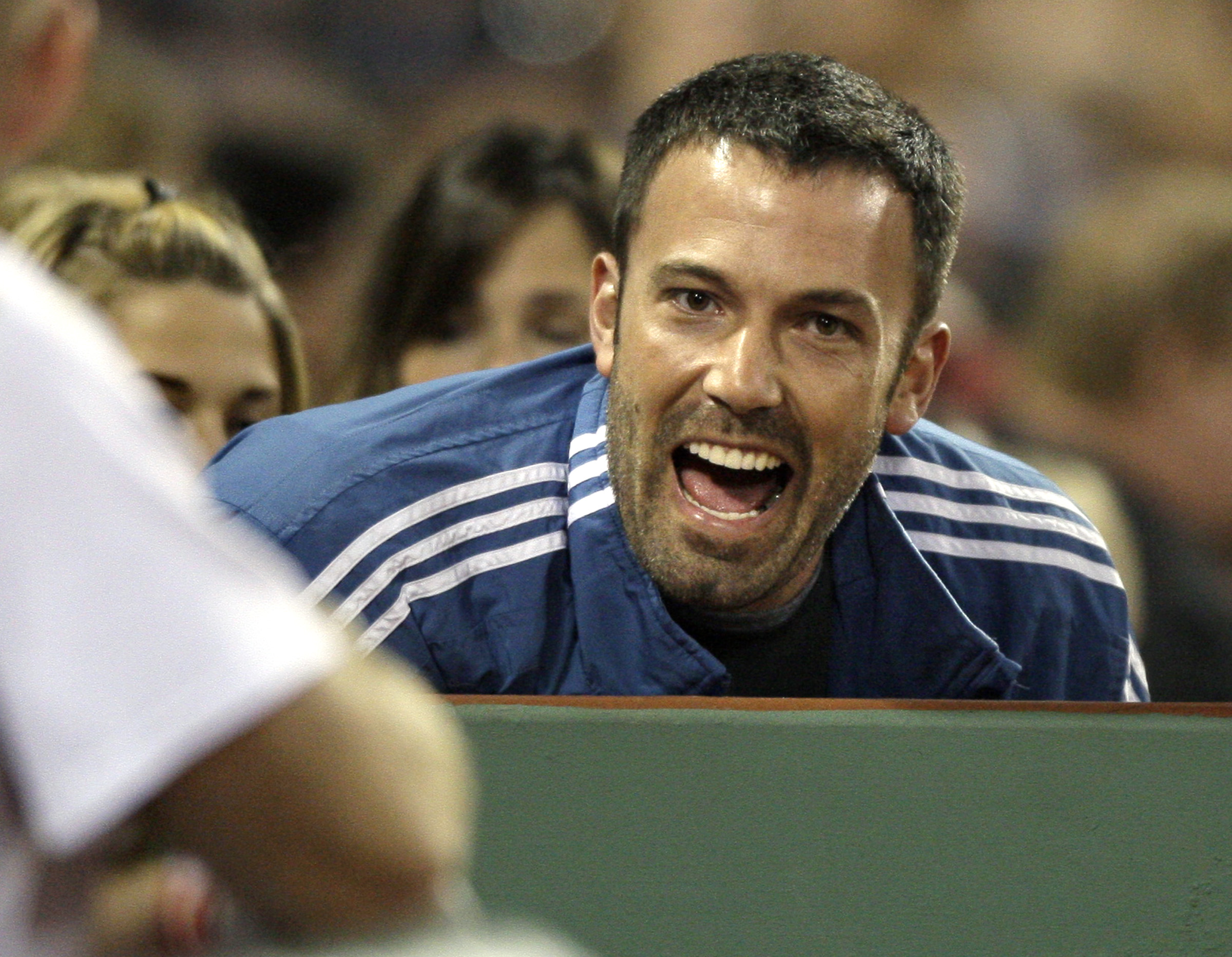 Actor Ben Affleck leans in to speak to players and coaches in the Boston Red Sox dugout during their baseball game against the Florida Marlins at Fenway Park in Boston Tuesday, June 16, 2009. (AP Photo/Elise Amendola)