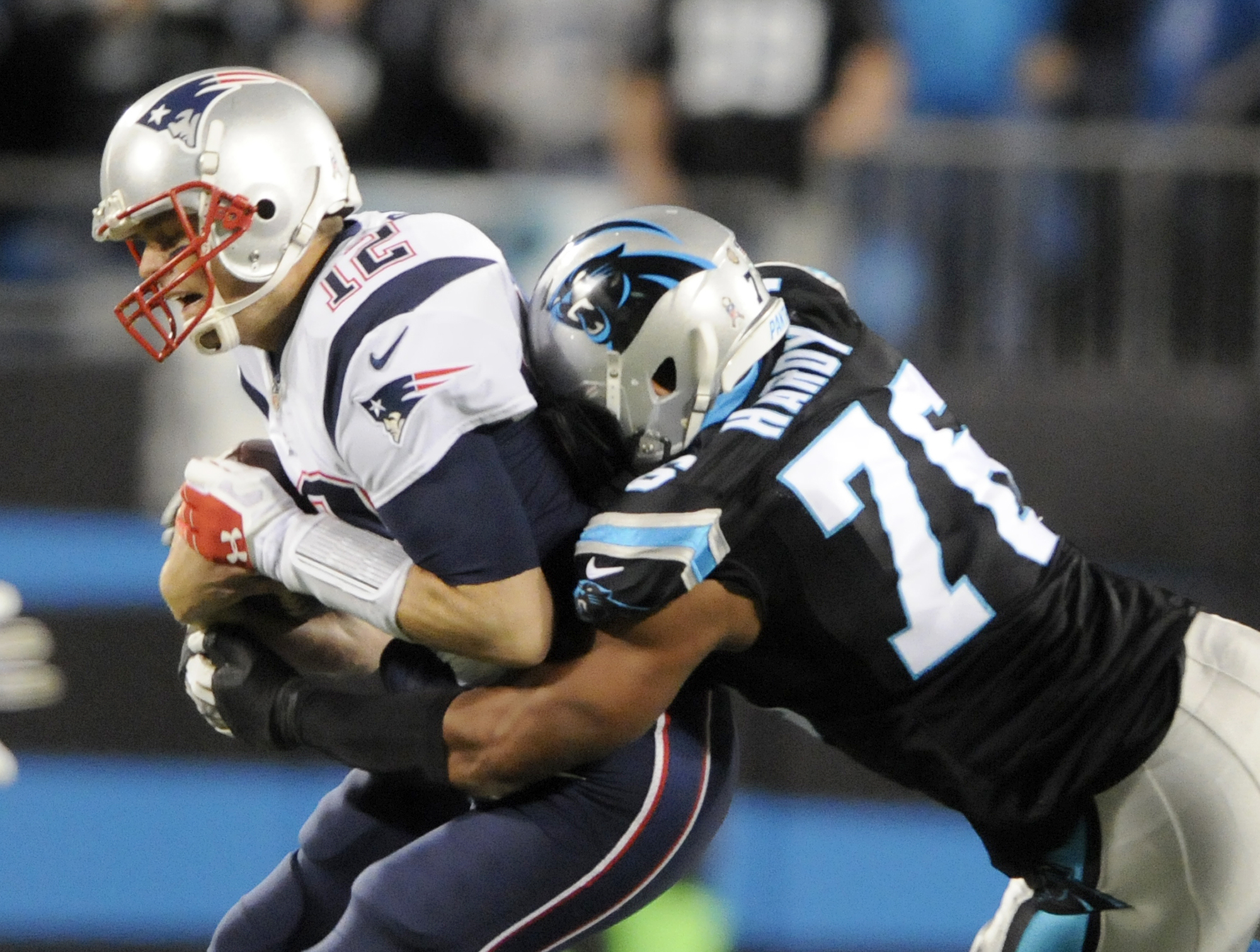 FILE - In this Nov. 18, 2013, file photo, New England Patriots' Tom Brady (12) is sacked by Carolina Panthers' Greg Hardy (76) during the first half of an NFL football game in Charlotte, N.C. Hardy was involved in a high-profile domestic violence case in