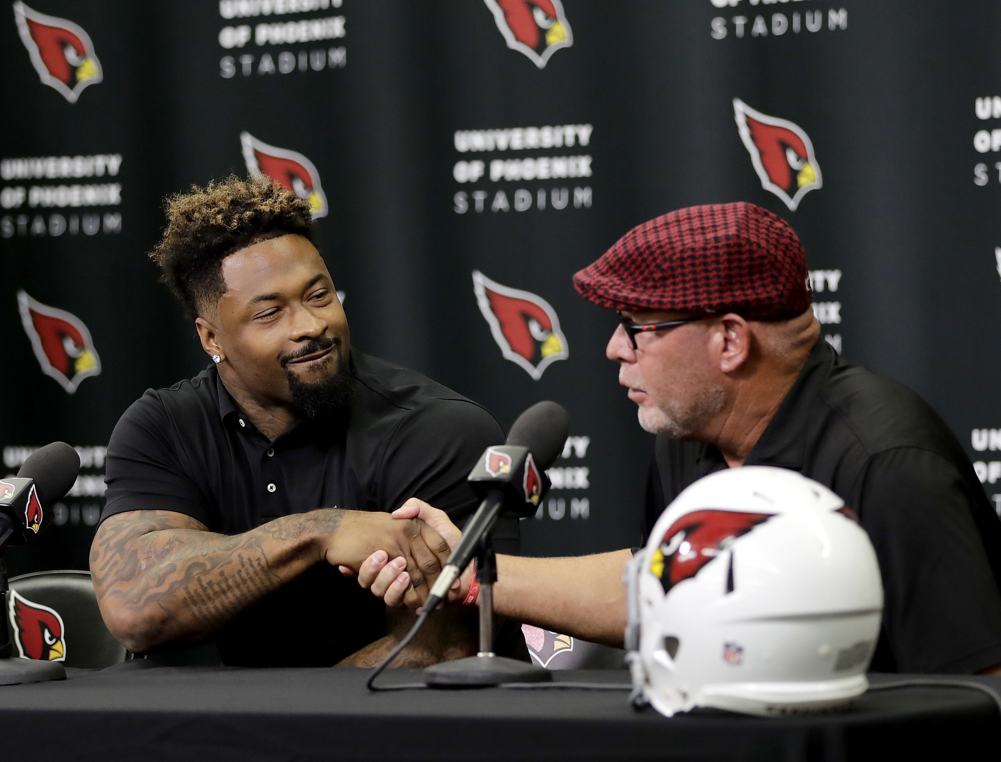 Darnell Dockett shakes hands with head coach Bruce Arians, right, after signing a contract with the Arizona Cardinals, Monday, July 25, 2016, in Tempe, Ariz. Dockett, who spent 11 seasons in Arizona, signed a one-day contract so he could retire as a Cardi