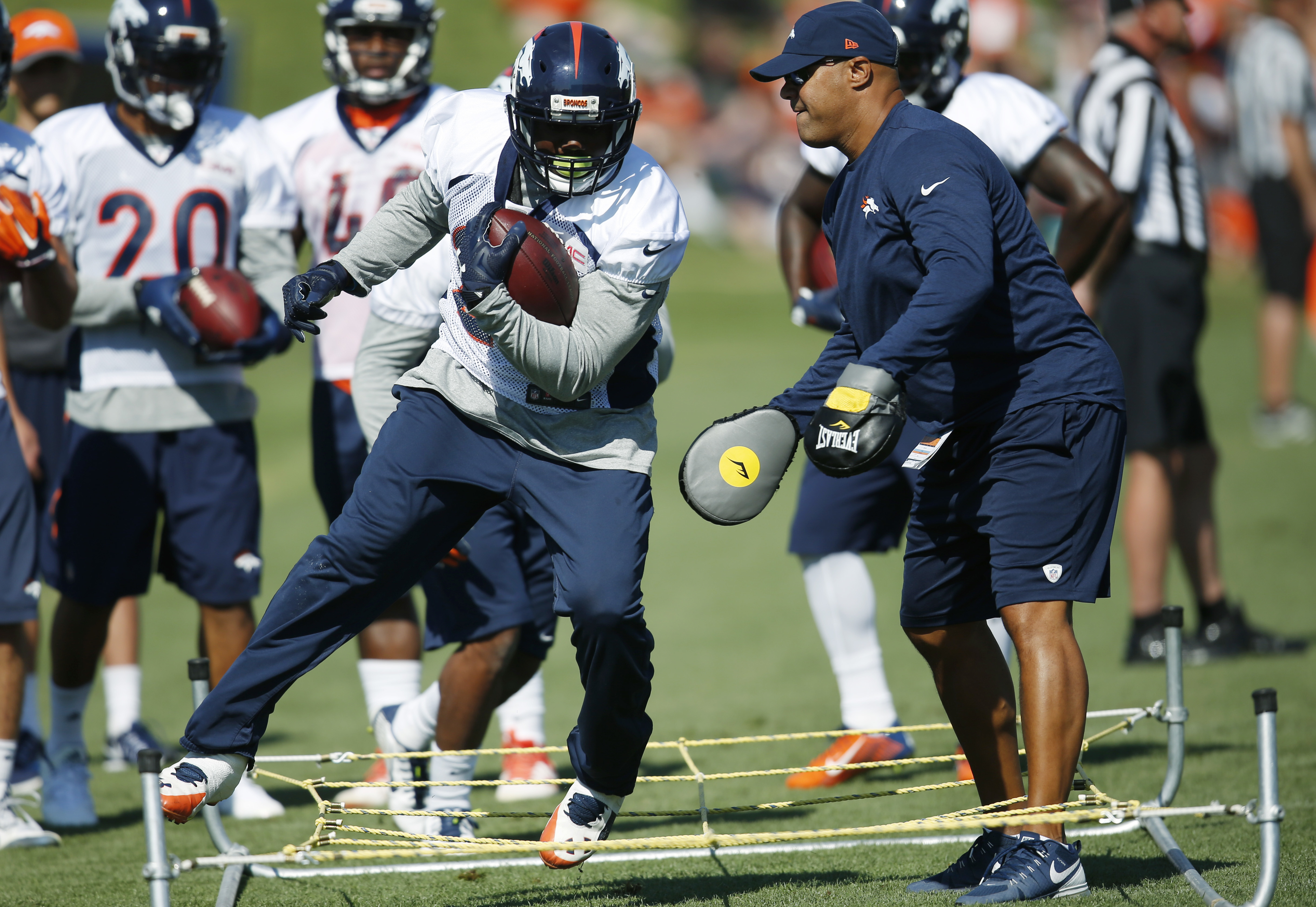Denver Broncos running back C.J. Anderson, left, takes part in drills as running backs coach Eric Studesville applies pressure with a pair of boxing gloves during the team's opening session of training camp Thursday, July 28, 2016 in Englewood, Colo. (AP