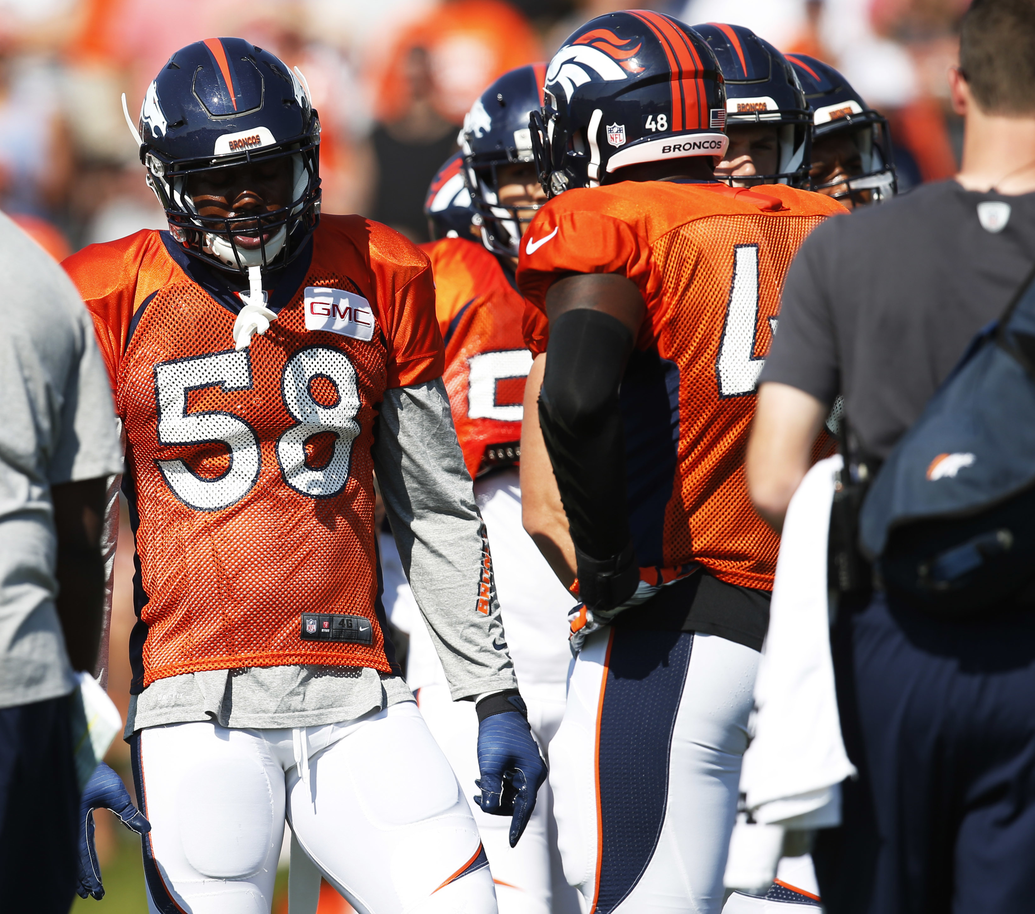 Denver Broncos outside linebackers Von Miller, left, and Shaquil Barrett confer as they take part in drills during the team's NFL football training camp Sunday, July 31, 2016 in Englewood, Colo. (AP Photo/David Zalubowski)