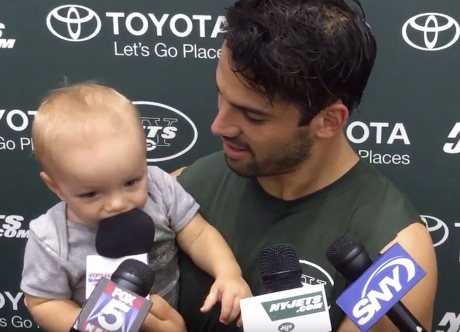 In this image from video, New York Jets wide receiver Eric Decker holds his 11-month-old son Eric II while addressing reporters after training camp practice in Florham Park, N.J., Sunday, July 31, 2016. (AP Photo/Dennis Waszak)