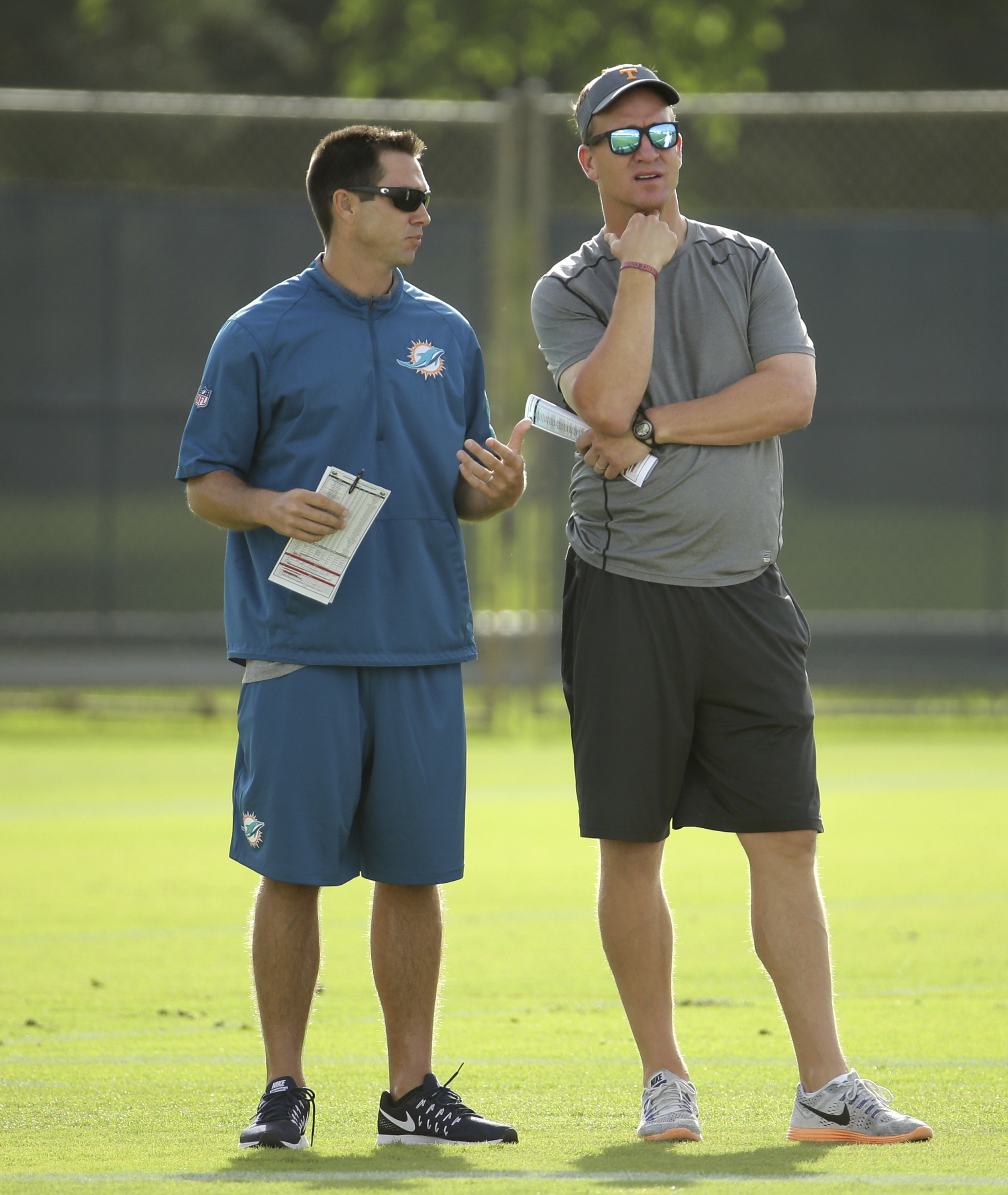 Former NFL quarterback Peyton Manning, right, watches Miami Dolphins NFL training camp with Joe Schoen, director of the Dolphins player personnel, Monday, Aug. 1, 2016 in Davie, Fla. (AP Photo/Lynne Sladky)