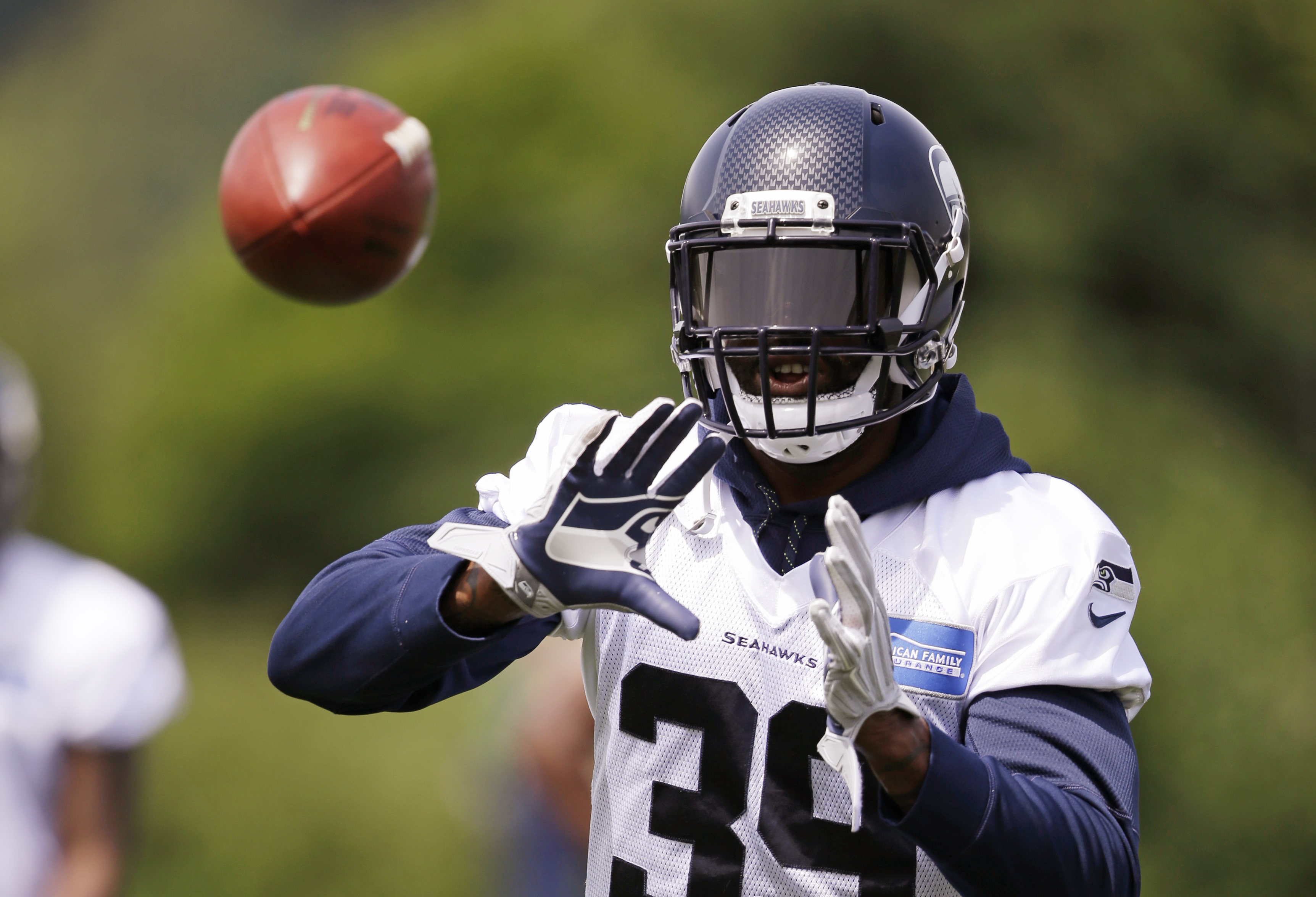 Seattle Seahawks' Brandon Browner reaches for a ball at an NFL football practice Wednesday, June 1, 2016, in Renton, Wash. (AP Photo/Elaine Thompson)