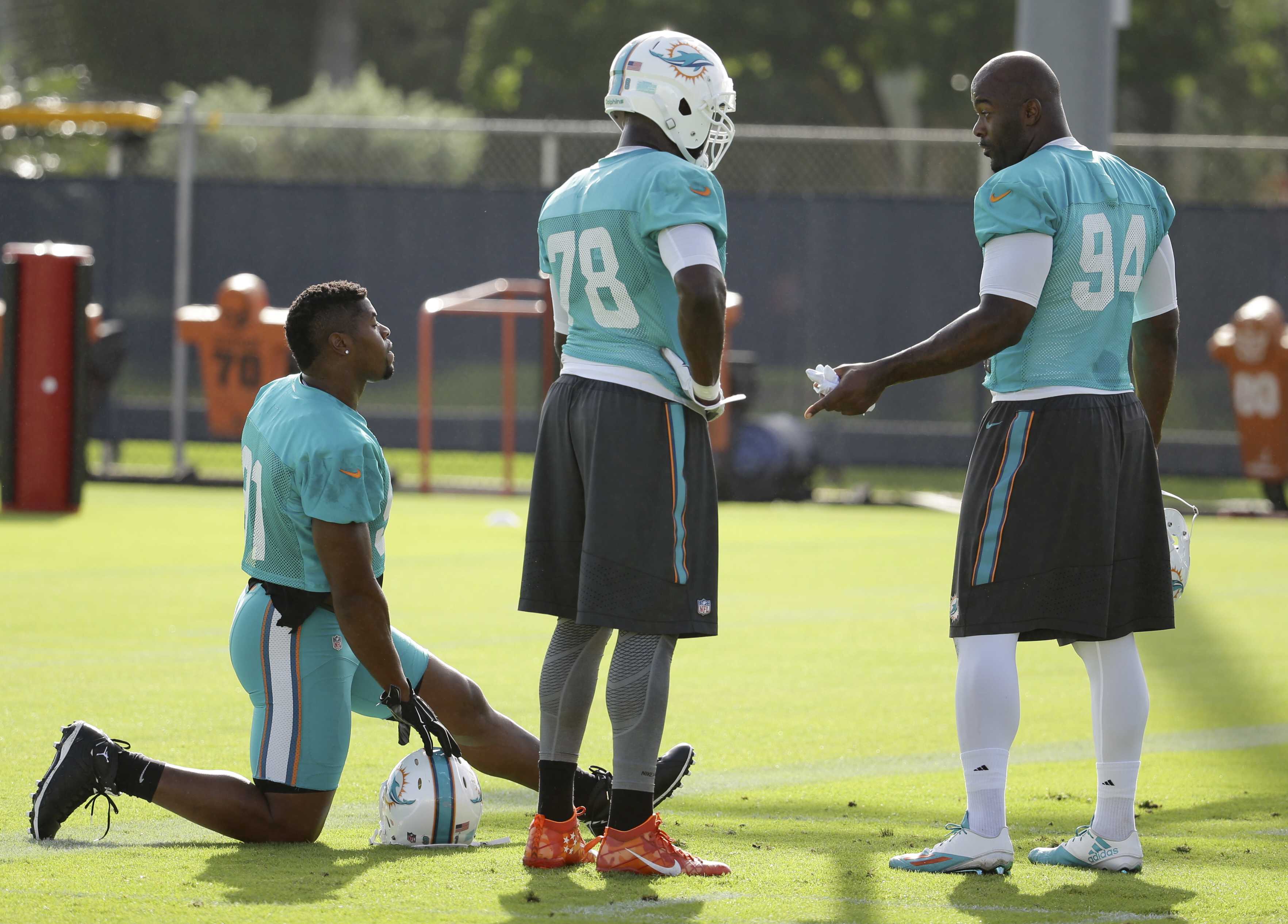 Miami Dolphins defensive end Cameron Wake, left, defensive end Terrence Fede (78) and defensive end Mario Williams (94) talk on the field Thursday, Aug. 4, 2016, during practice at NFL football training camp in Davie, Fla. (AP Photo/Lynne Sladky)
