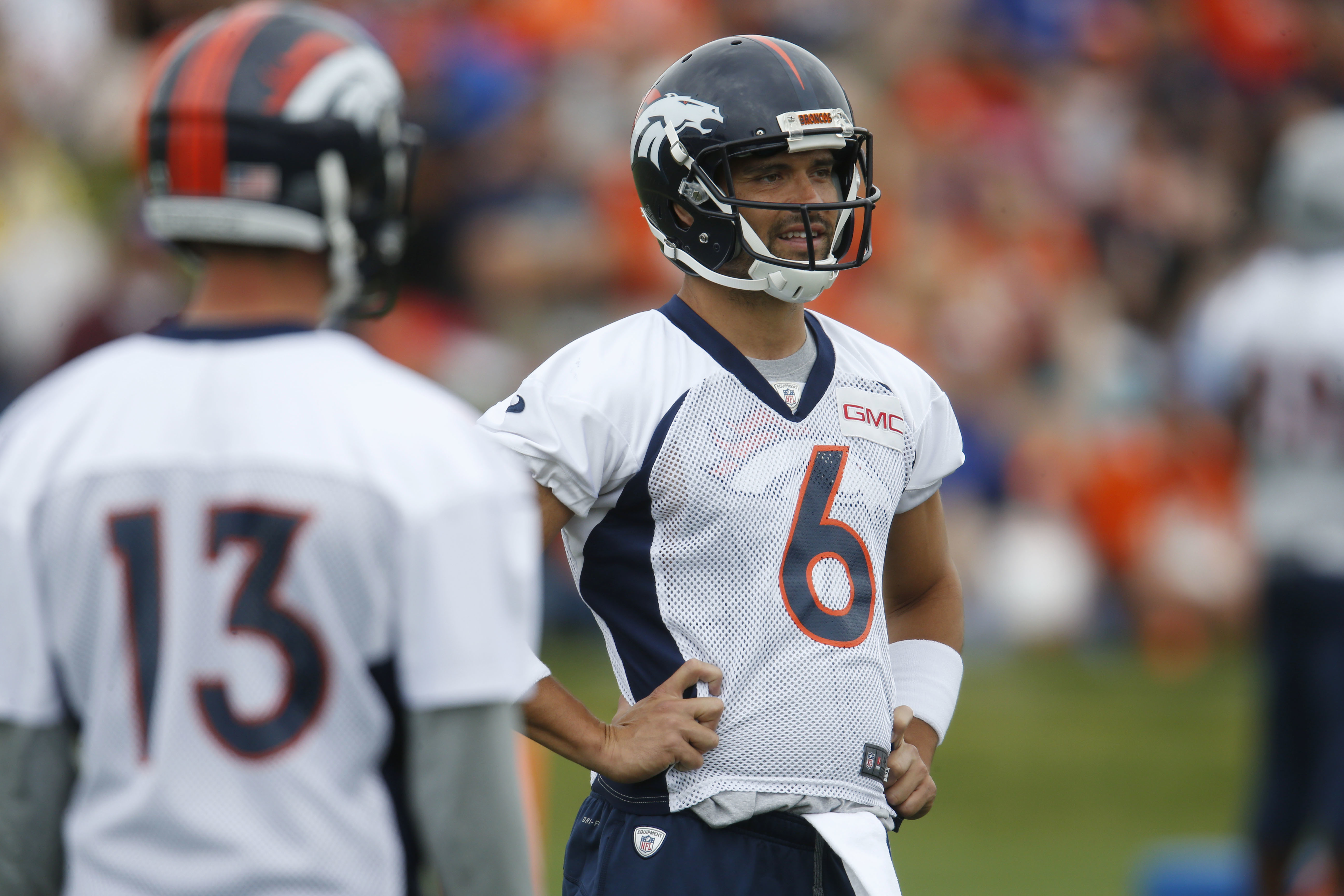 Denver Broncos quarterback Mark Sanchez, back, smiles as he jokes with quarterback Trevor Siemian as they take part in drills at the team's NFL football training camp Friday, Aug. 5, 2016 in Englewood, Colo. (AP Photo/David Zalubowski)