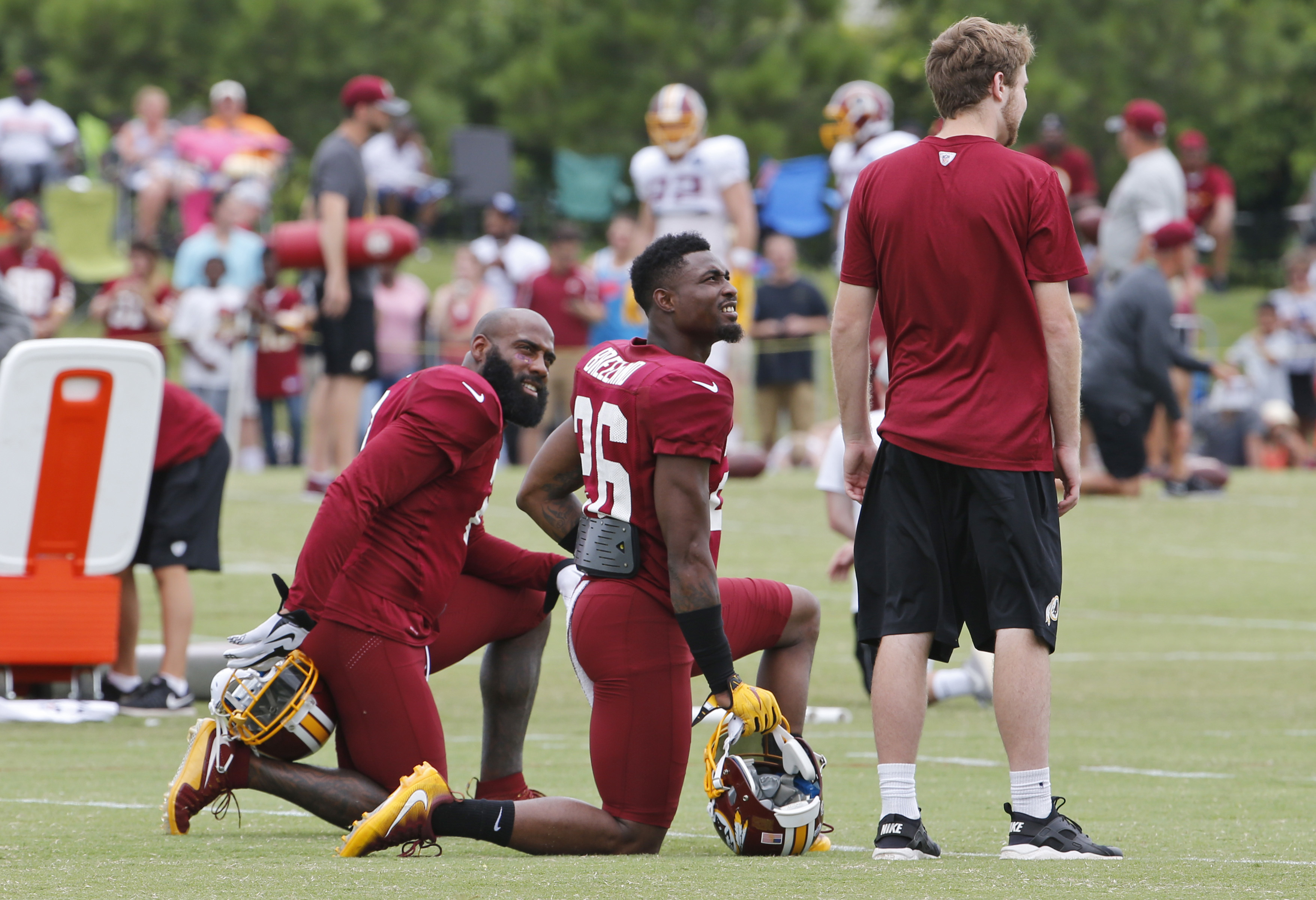 Washington Redskins DeAngelo Hall, left, and Bashaud Breeland, center, talk to a trainer during the afternoon practice at the Washington Redskins NFL football teams training camp in Richmond, Va., Friday, Aug. 5, 2016. (AP Photo/Steve Helber)