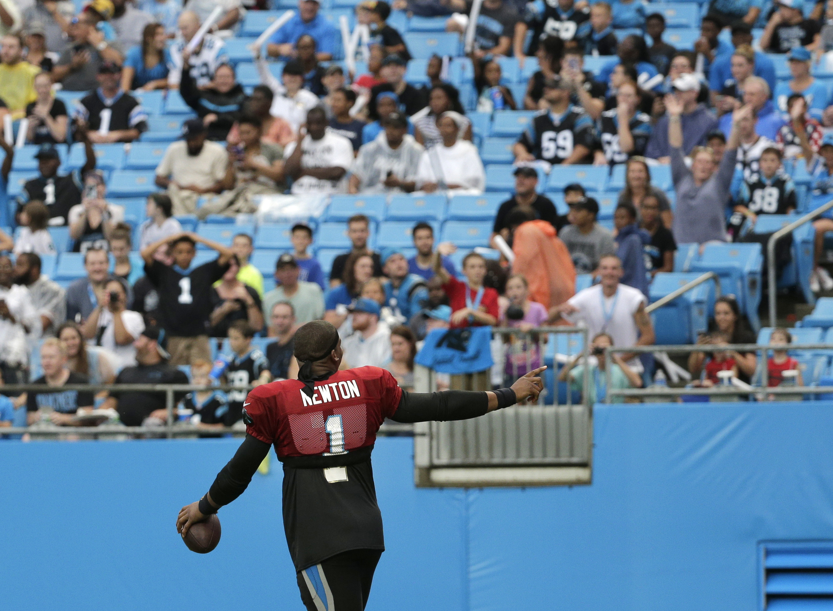 Carolina Panthers' Cam Newton points to the crowd at the team's annual Fan Fest practice during NFL training camp in Charlotte, N.C., Friday, Aug. 5, 2016. (AP Photo/Chuck Burton)