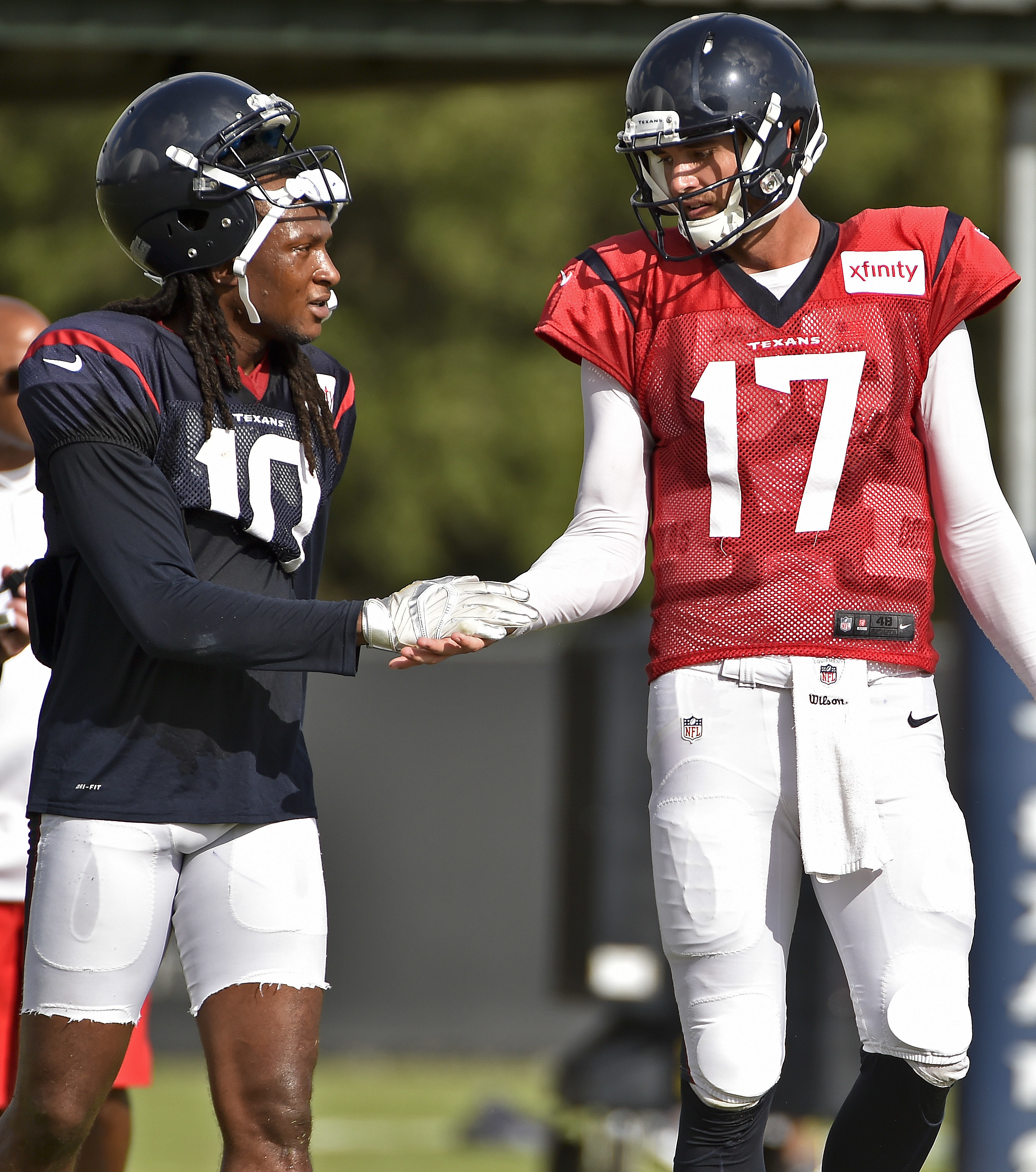 Houston Texans wide receiver DeAndre Hopkins, left, shakes hands with Houston Texans quarterback Brock Osweiler during a practice at the NFL football team's training camp, Saturday, Aug. 6, 2016, in Houston. (AP Photo/Eric Christian Smith)