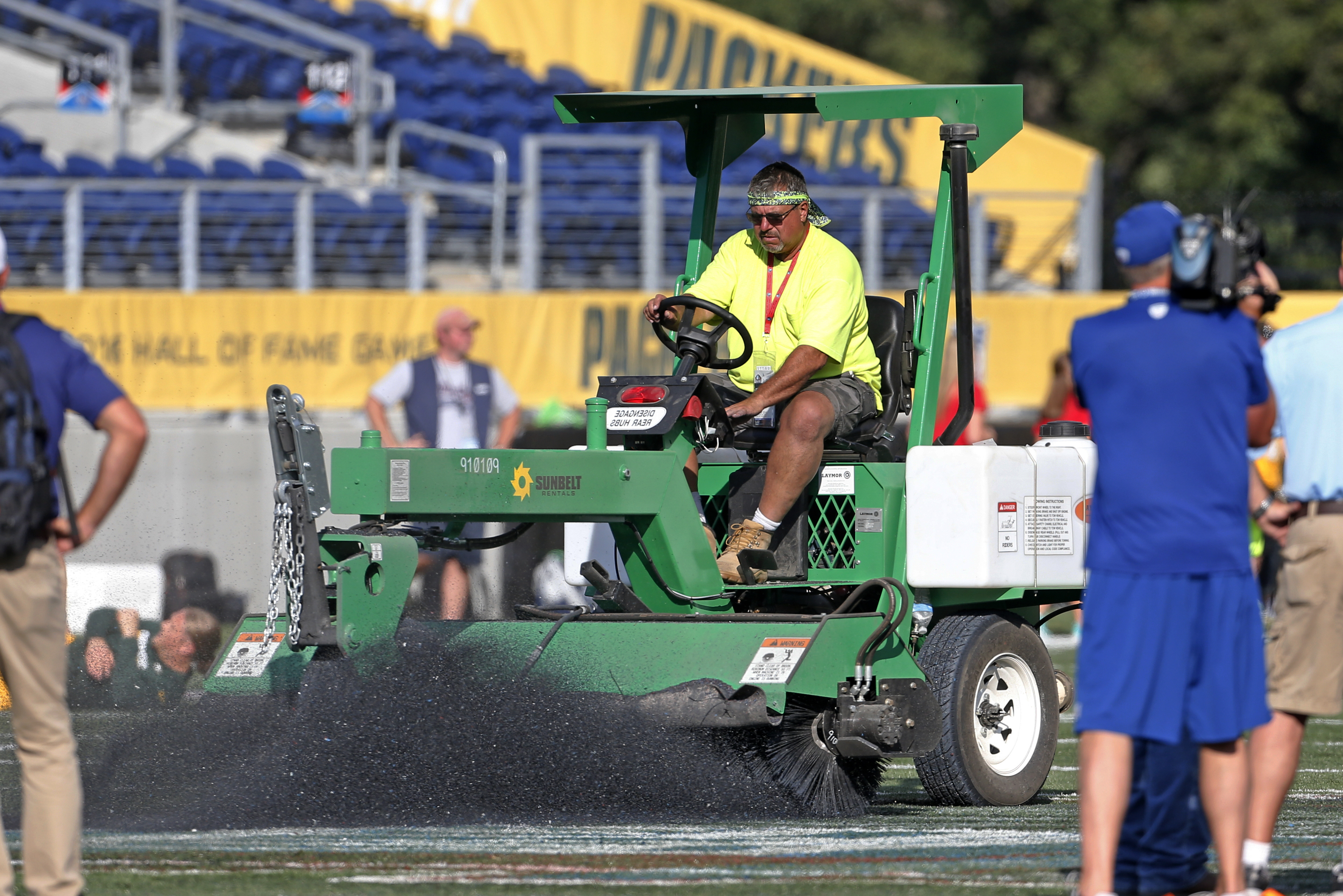 The ground crew at Tom Benson Hall of Fame Stadium scrape the painted logo off the center of the field before an NFL preseason football game between the Green Bay Packers and the Indianapolis Colts, Sunday, Aug. 7, 2016, in Canton, Ohio. (AP Photo/Ron Sch