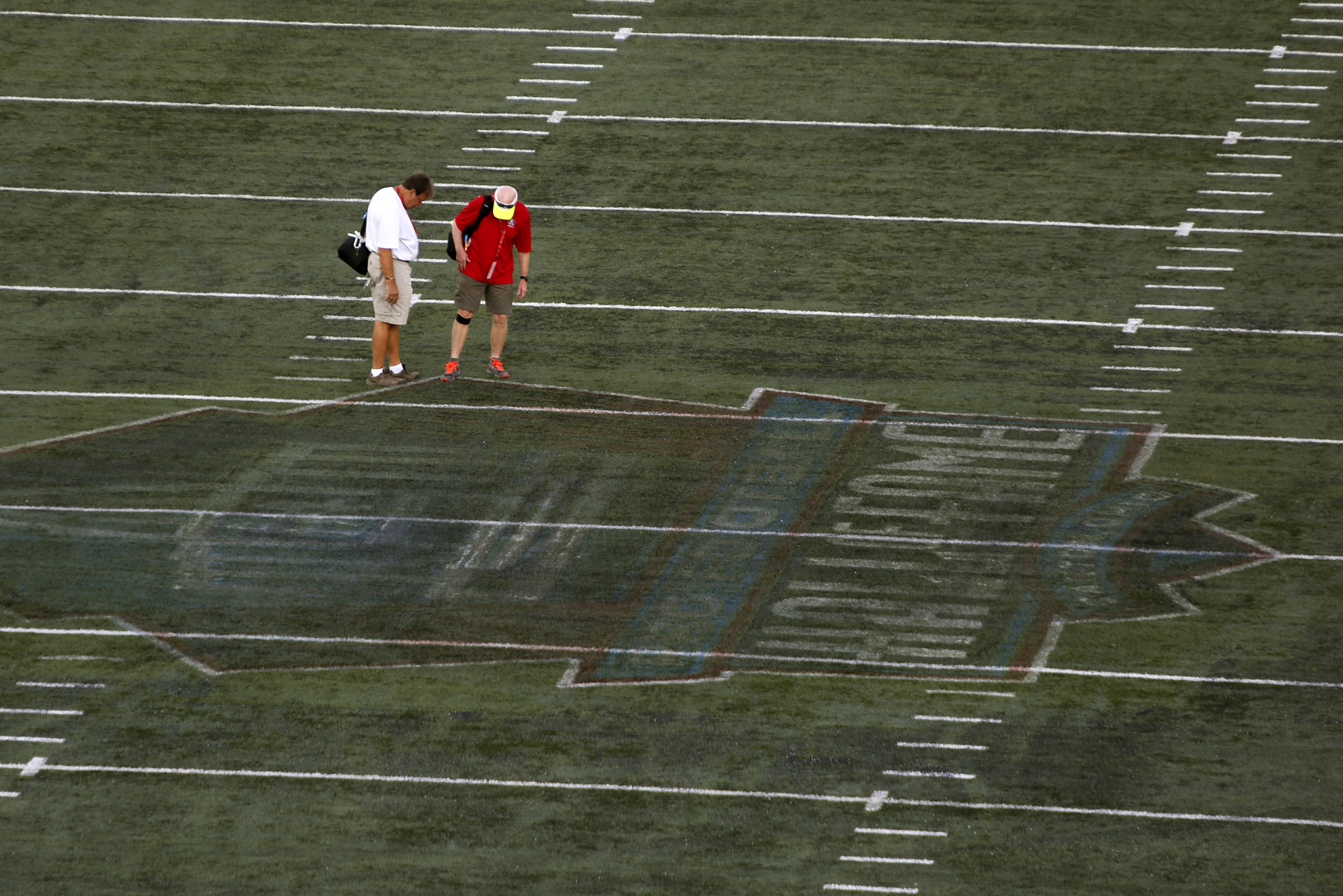 The damaged field at Tom Benson Hall of Fame Stadium is inspected after the preseason NFL football game was cancelled due to unsafe field conditions caused by the painted logo at midfield, Sunday, Aug. 7, 2016, in Canton, Ohio. (AP Photo/Gene J. Puskar)