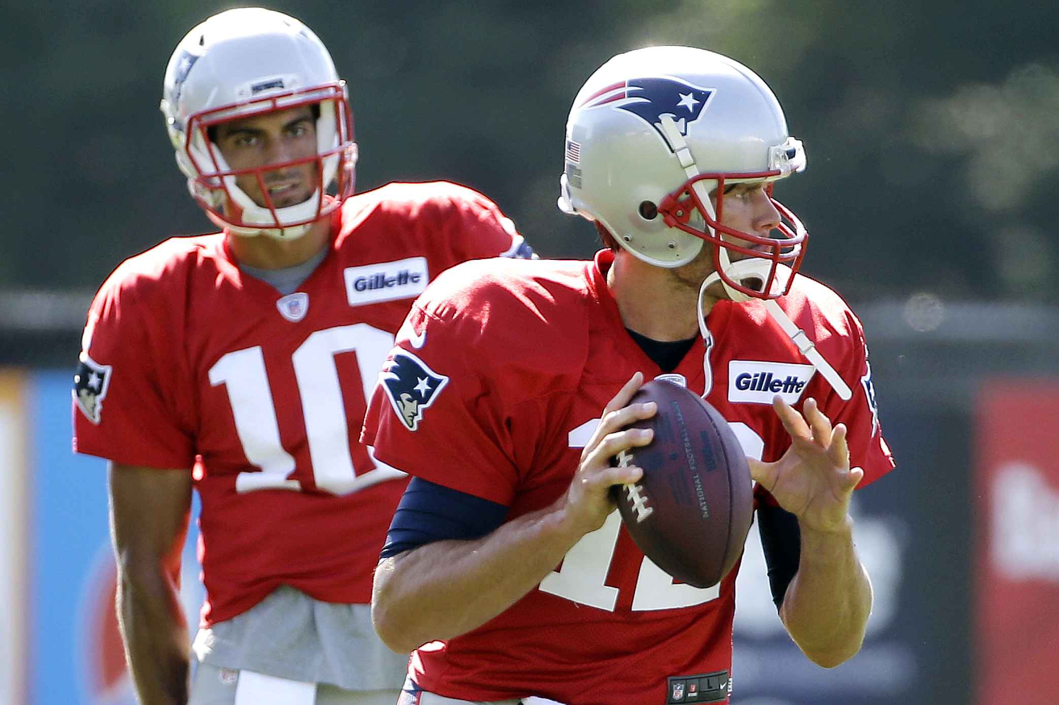 FILE - In this Tuesday, Aug. 9, 2016, file photo, New England Patriots quarterback Tom Brady (12) gets set to throw a pass as quarterback Jimmy Garoppolo (10) watches during NFL football training camp in Foxborough, Mass. This is one unusual summer for th