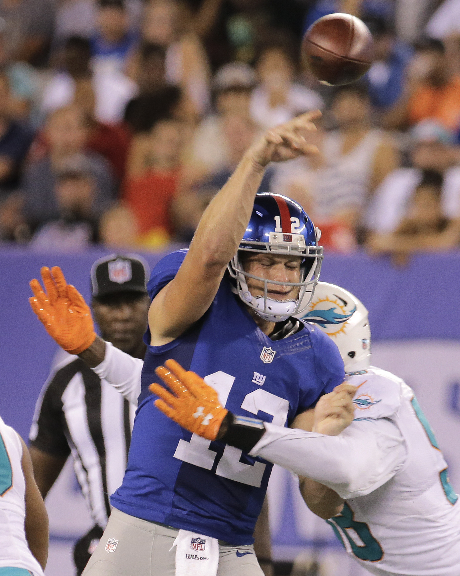 New York Giants quarterback Ryan Nassib (12) is hit by Miami Dolphins defensive end Chris McCain (58) during the first quarter of an NFL football game, Friday, Aug. 12, 2016, in East Rutherford, N.J. (AP Photo/Ray Stubblebine)