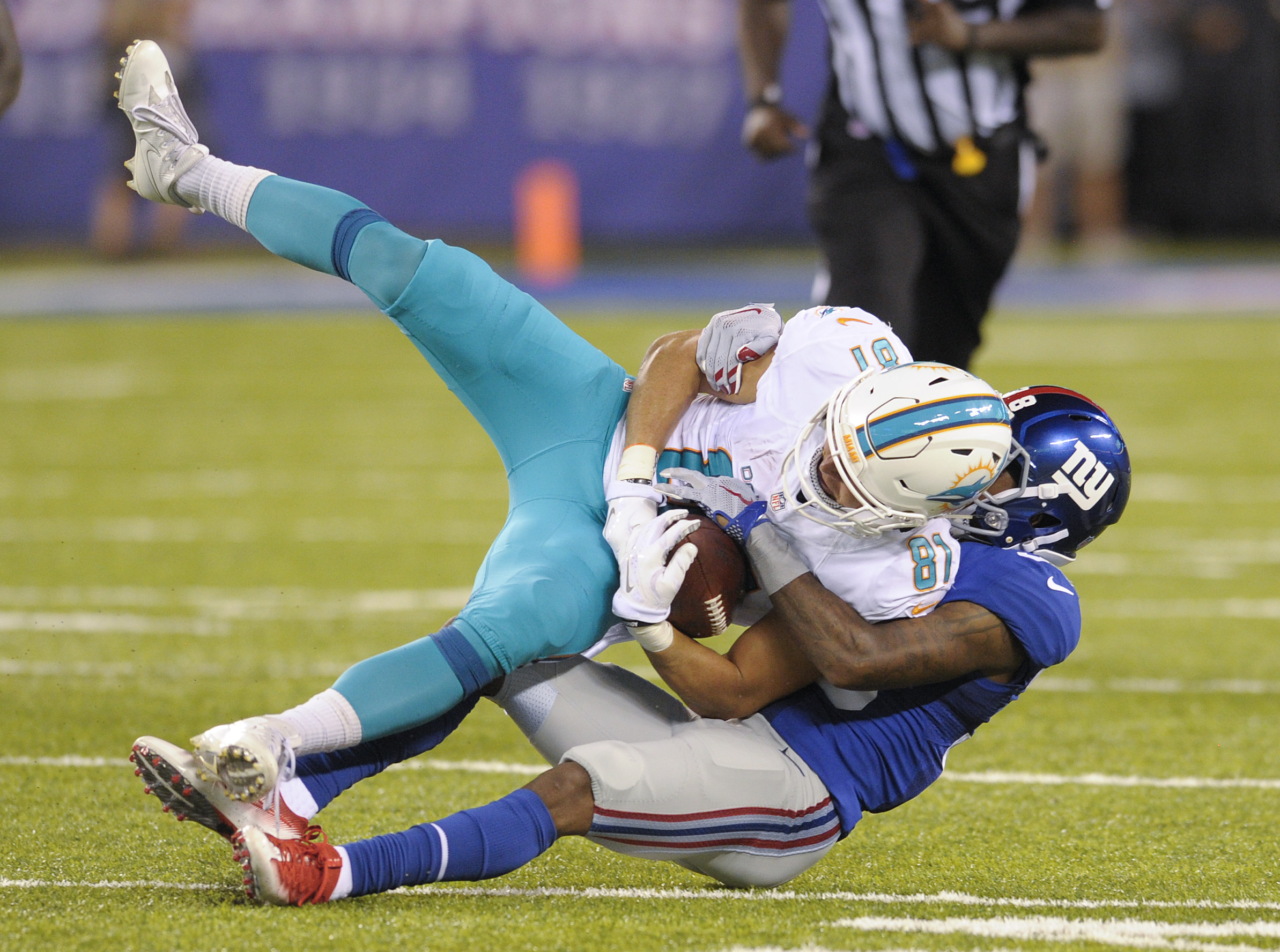 Miami Dolphins wide receiver A.J. Cruz (81) is brought down by New York Giants defensive back Donte Deayon (38) during the second quarter of a preseason NFL football game, Friday, Aug. 12, 2016, in East Rutherford, N.J. (AP Photo/Bill Kostroun)