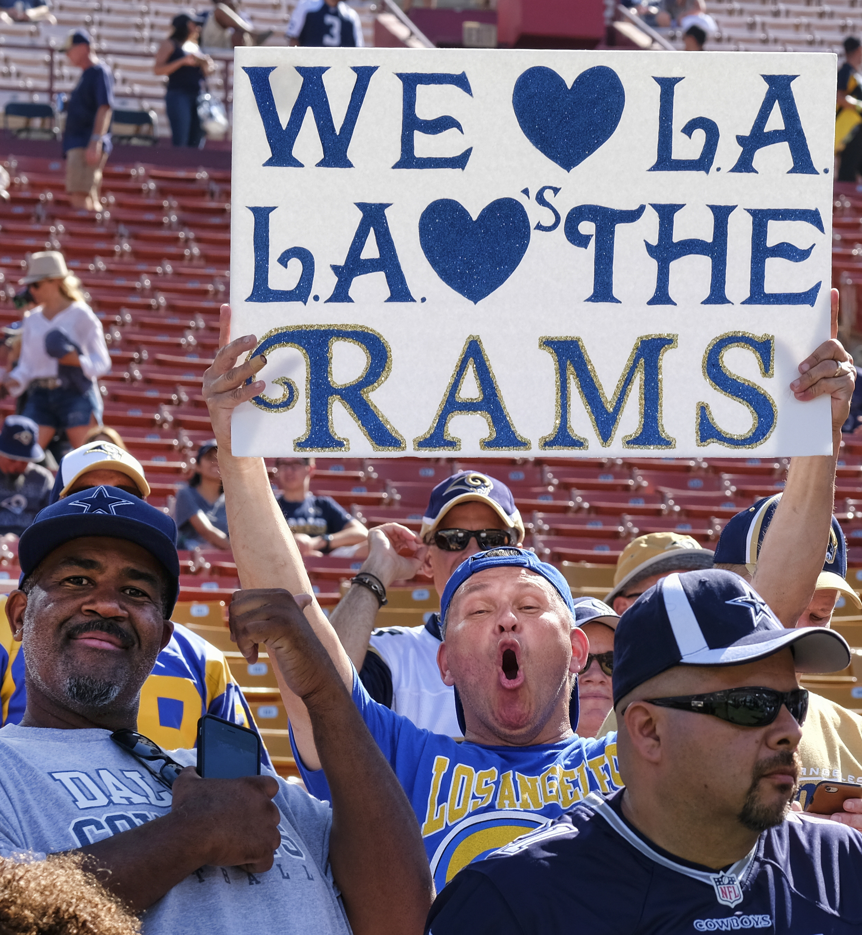 A Los Angeles Rams fan displays a sign while waiting for his team to arrive at Los Angeles Memorial Coliseum on Saturday, Aug. 13, 2016. Los Angeles fans celebrate the return of the NFL and their long-lost Los Angeles Rams to the city at the team's first