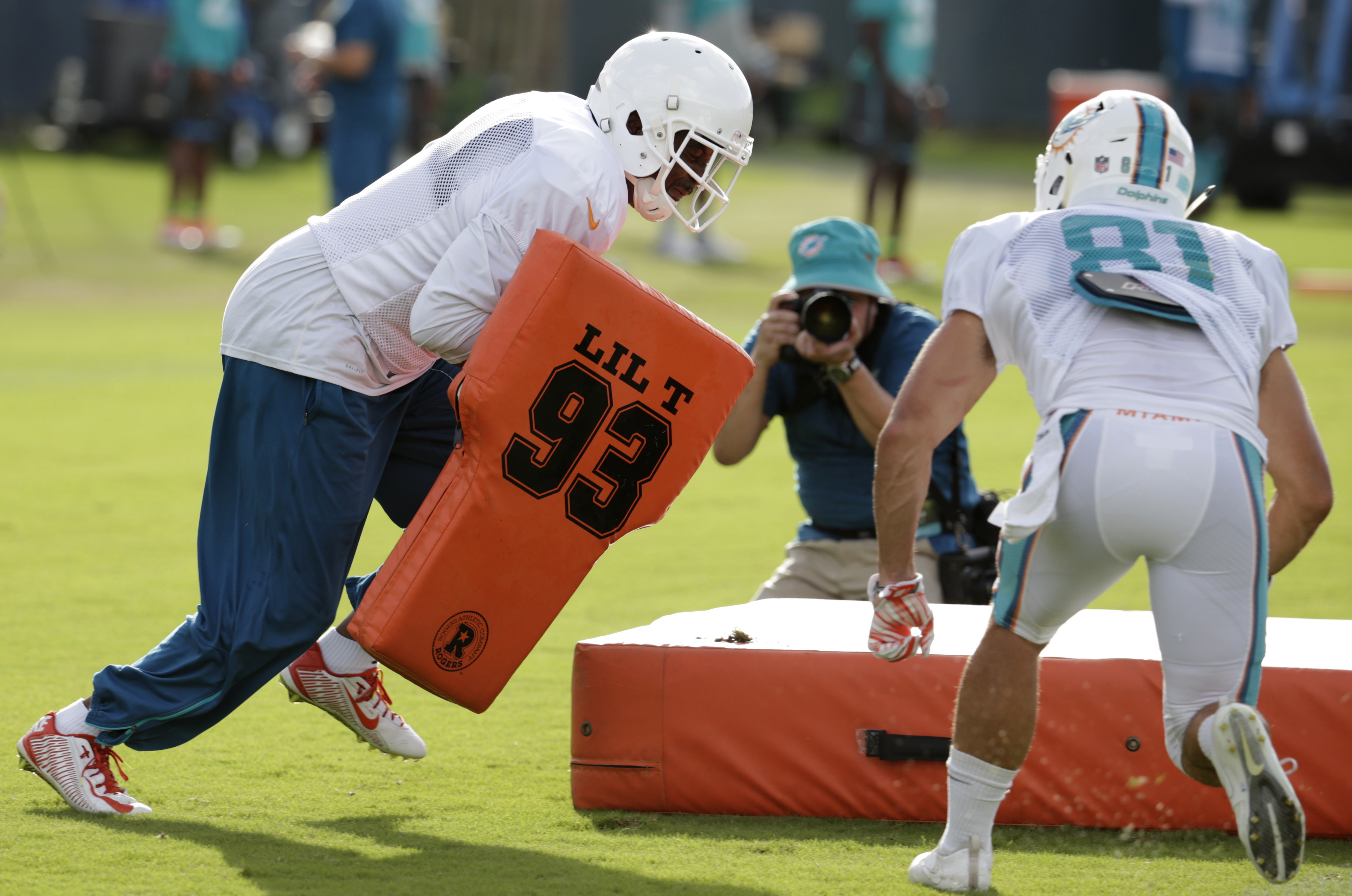 Miami Dolphins wide receivers coach Shawn Jefferson, left, wears pads as he does drills with wide receiver A.J. Cruz (81), Tuesday, Aug. 16, 2016, during practice at NFL football training camp in Davie, Fla. (AP Photo/Lynne Sladky)