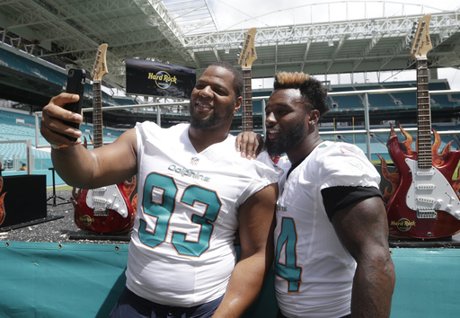 Miami Dolphins defensive tackle Ndamukong Suh (93) and wide receiver Jarvis Landry (14) take a selfie following a ceremony for a stadium naming rights agreement between the Miami Dolphins NFL football team and Hard Rock International, Wednesday, Aug. 17,