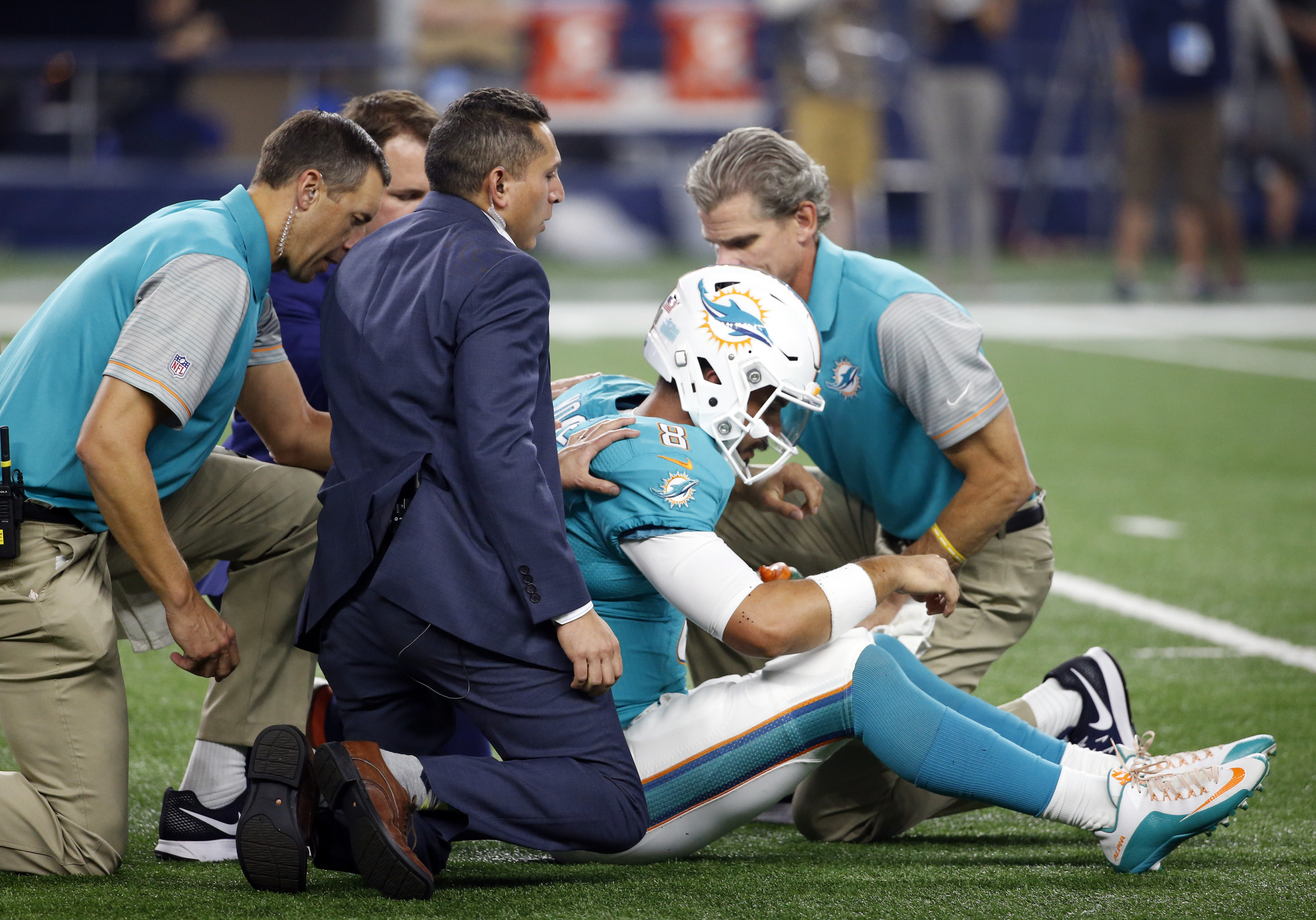 Miami Dolphins quarterback Matt Moore (8) is helped by staff after suffering an unknown injury in the first half of an NFL preseason football game against the Dallas Cowboys, Friday, Aug. 19, 2016, in Arlington, Texas. (AP Photo/Michael Ainsworth)