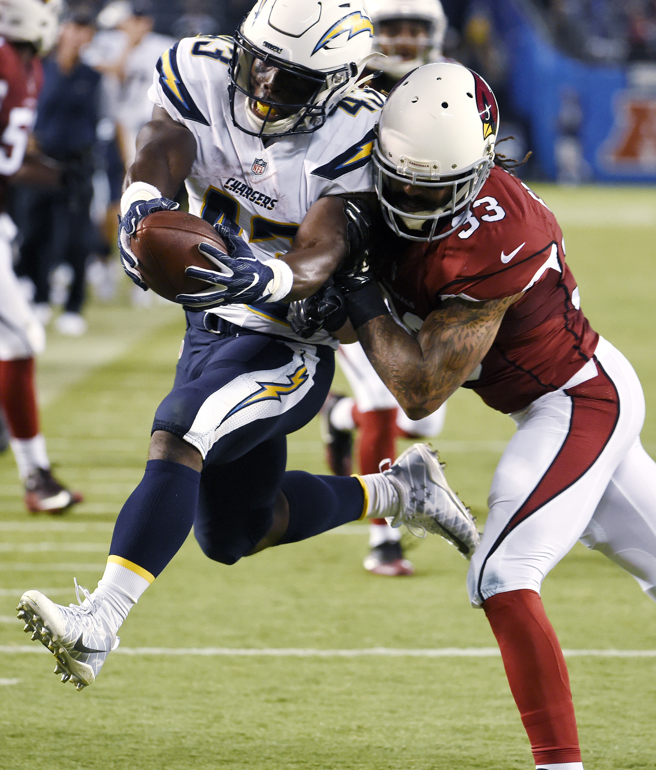 San Diego Chargers running back Branden Oliver, left, is tackled by Arizona Cardinals defensive back Matthias Farley during the second half of a preseason NFL football game, Friday, Aug. 19, 2016, in San Diego. (AP Photo/Denis Poroy)