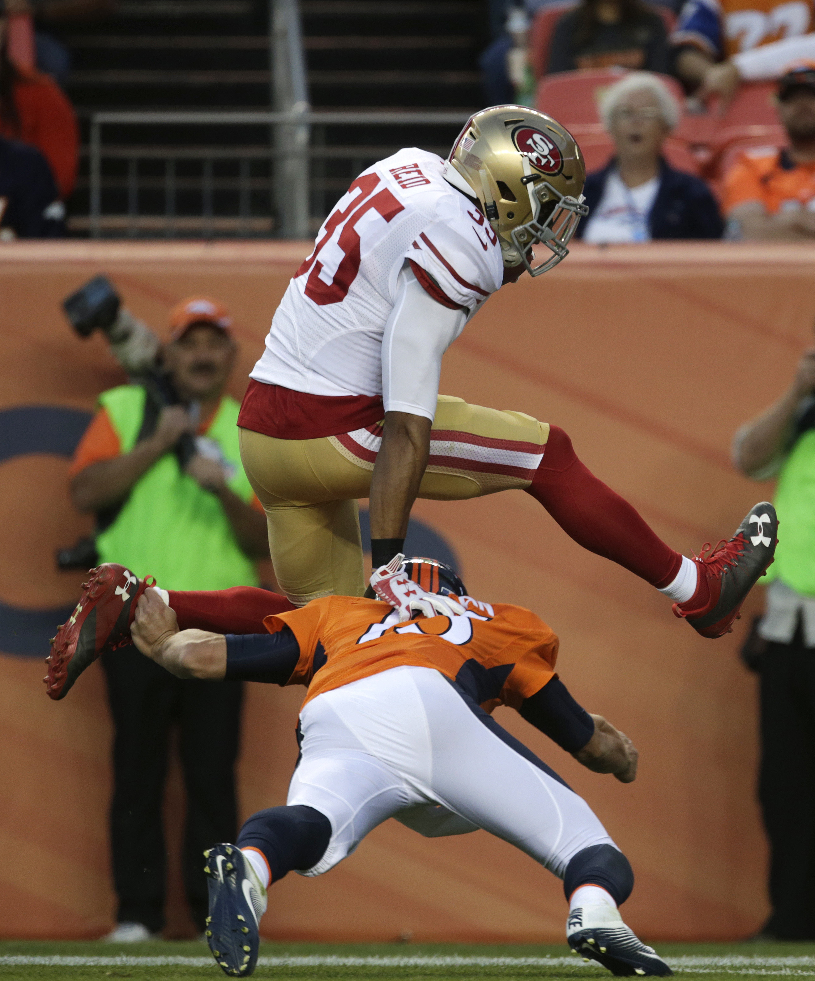 San Francisco 49ers free safety Eric Reid leaps over Denver Broncos quarterback Trevor Siemian as Reid runs for a touchdown after intercepting a pass from Siemian during the first half of a preseason NFL football game, Saturday, Aug. 20, 2016, in Denver.