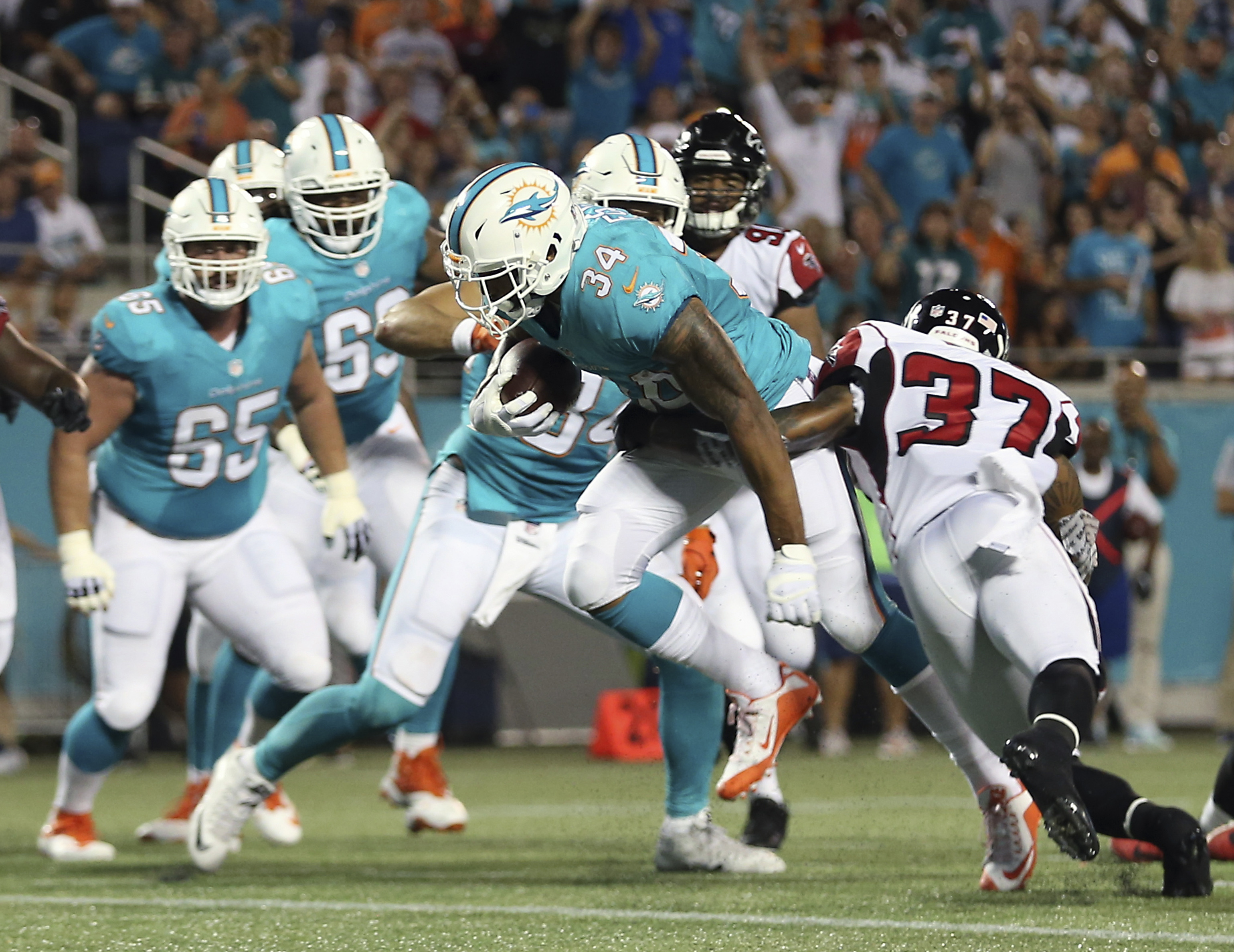 Miami Dolphins' Arian Foster (34) runs for a 2-yard touchdown past Atlanta Falcons free safety Ricardo Allen (37) during the first half of an NFL preseason football game in Orlando, Fla., Thursday, Aug. 25, 2016.(AP Photo/Willie J. Allen Jr.)