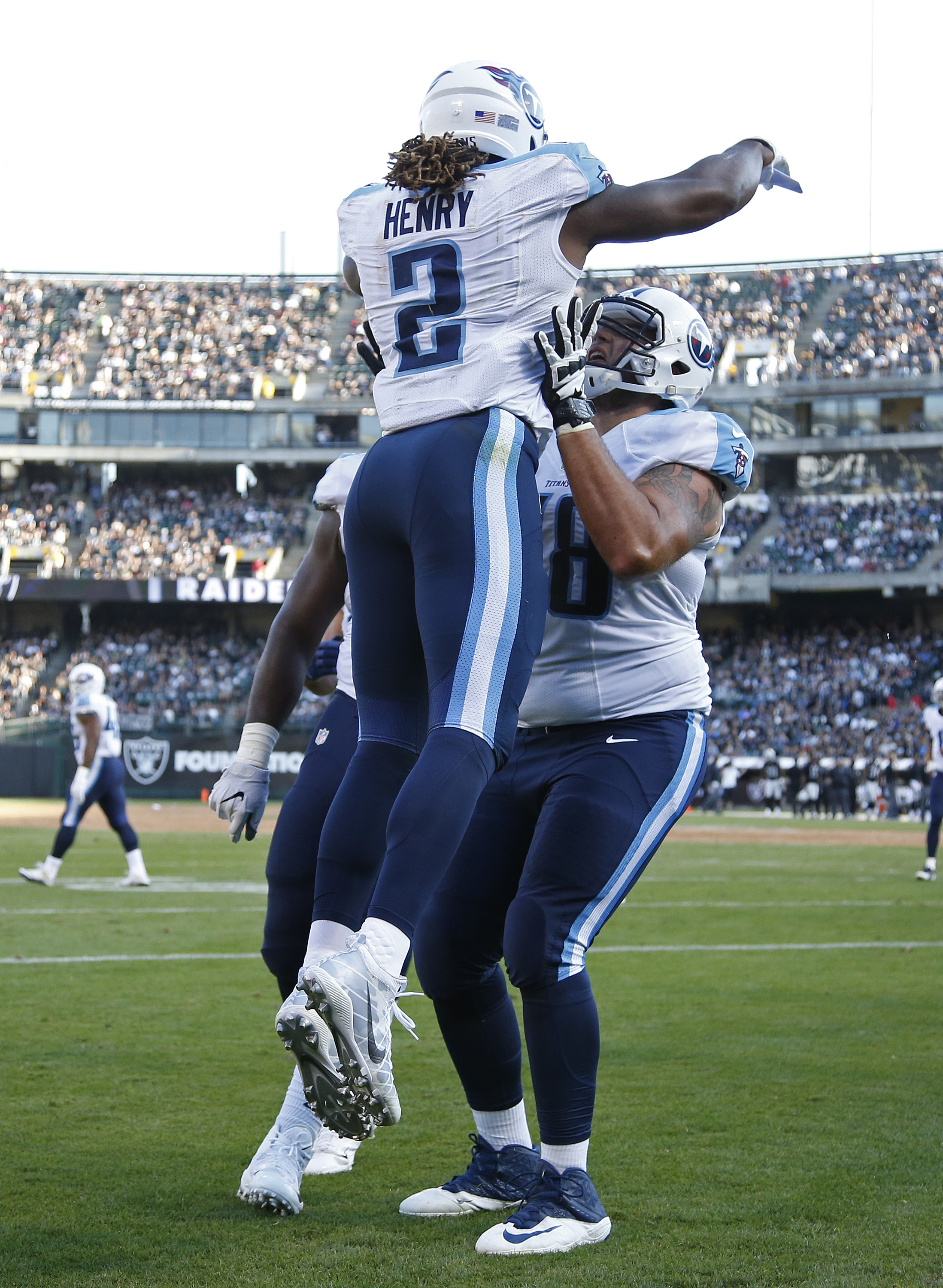 Tennessee Titans running back Derrick Henry, left, is greeted by teammate Jack Conklin, right, after scoring a touchdown during the first half of an NFL preseason football game against the Oakland Raiders Saturday, Aug. 27, 2016, in Oakland, Calif. (AP Ph