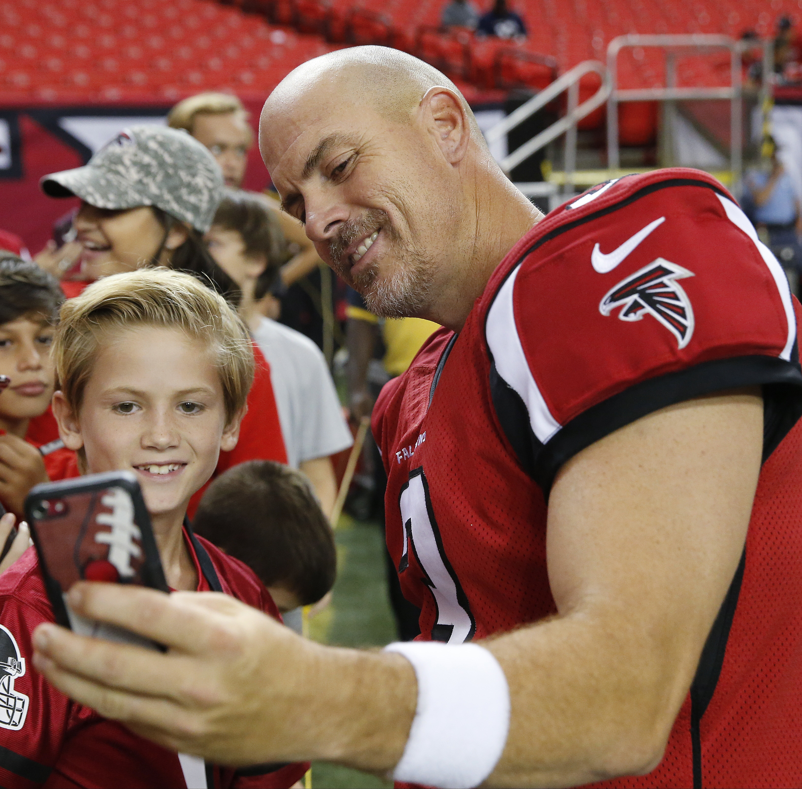Atlanta Falcons kicker Matt Bryant, right, shoots a photo with a young fan on the turf before the first half of a preseason NFL football game between the Atlanta Falcons and the Jacksonville Jaguars, Thursday, Sept. 1, 2016, in Atlanta. (AP Photo/John Baz