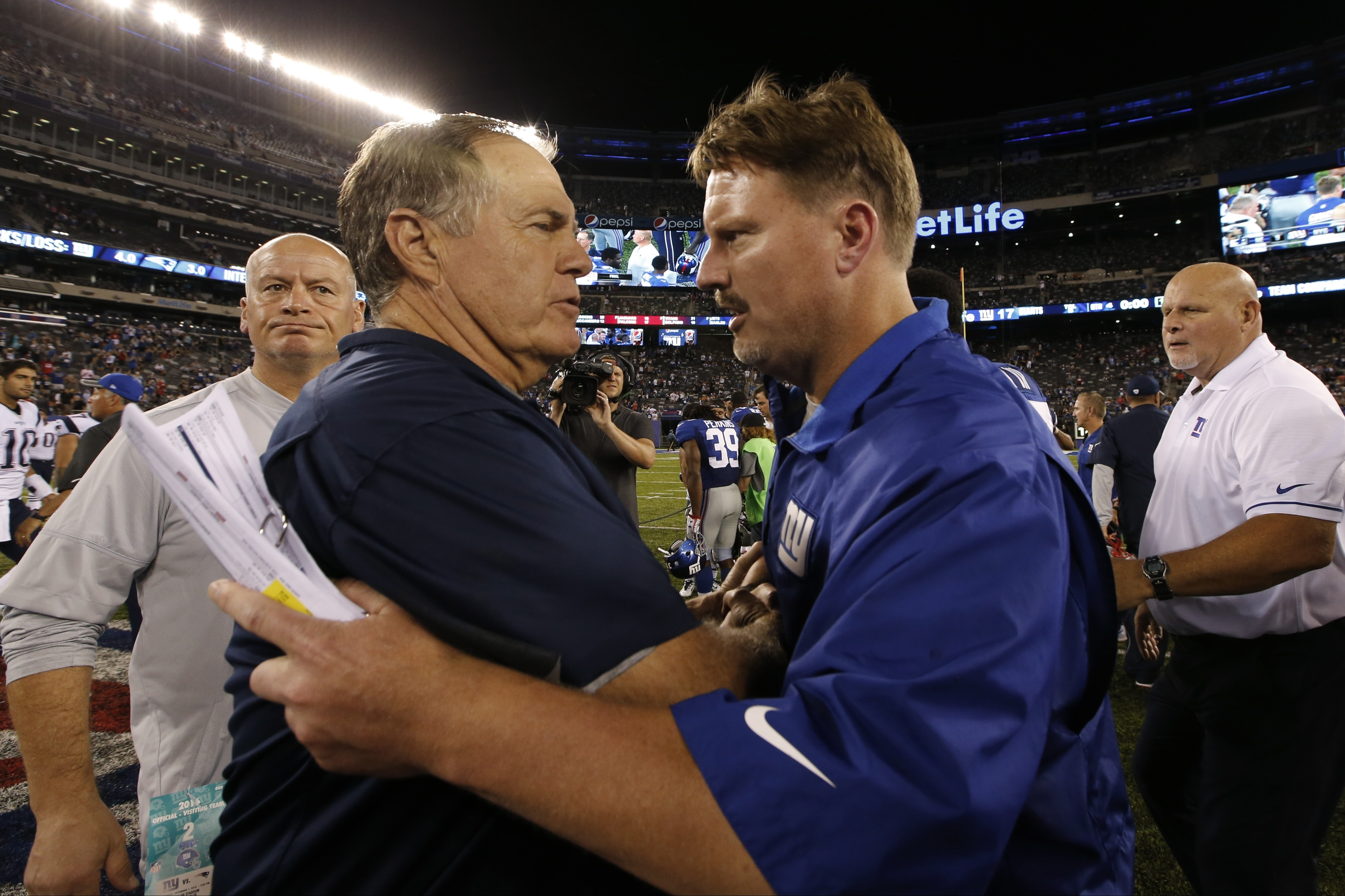New England Patriots coach Bill Belichick, left, and New York Giants coach Ben McAdoo, right, meet after a preseason NFL football game Thursday, Sept. 1, 2016, in East Rutherford, N.J. The Giants won 17-9. (AP Photo/Kathy Willens)