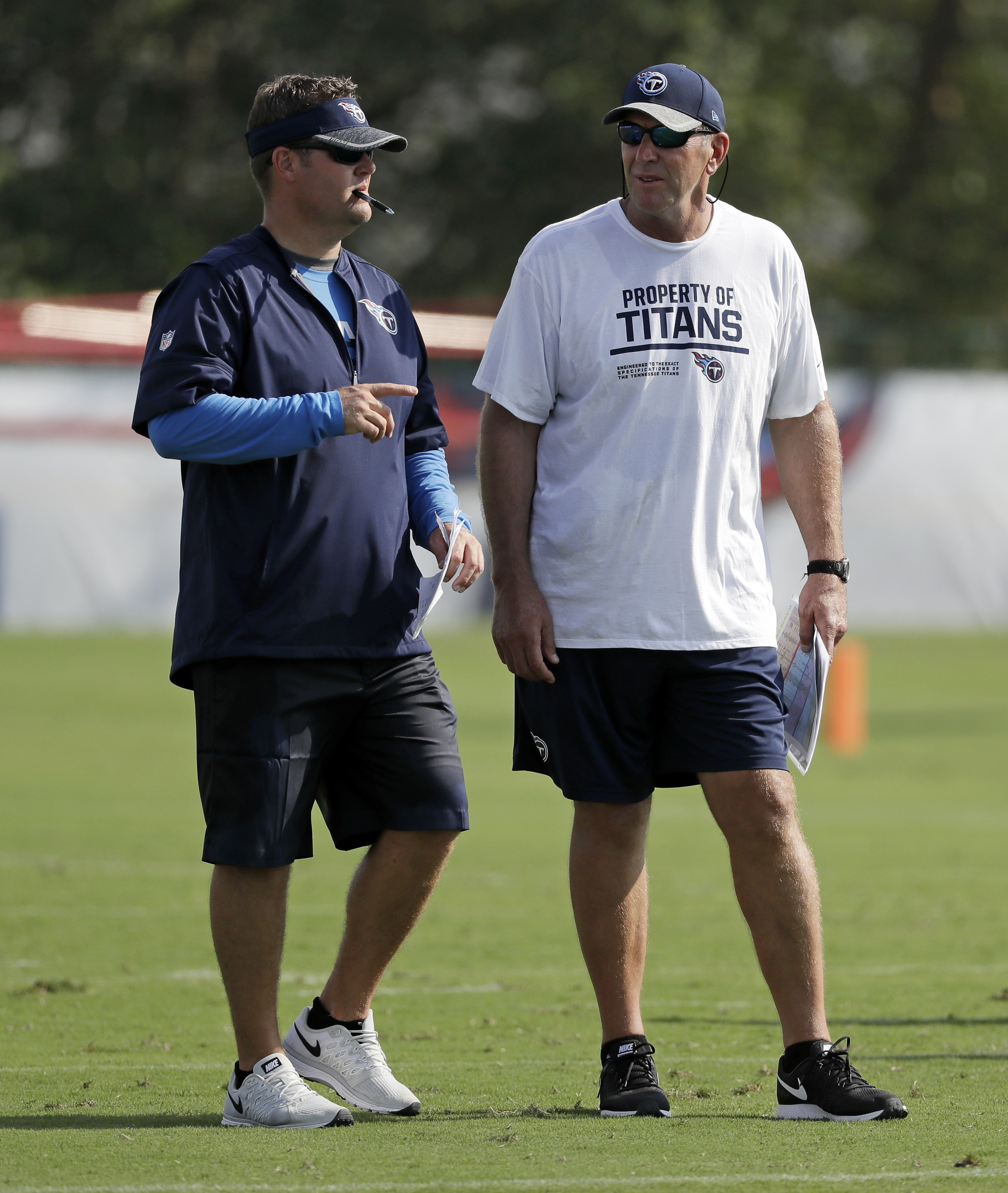 FILE - In this July 30, 2016, file photo, Tennessee Titans head coach Mike Mularkey, right, talks with general manager Jon Robinson during NFL football training camp, in Nashville, Tenn. First-year general manager Robinson and coach Mularkey have made it