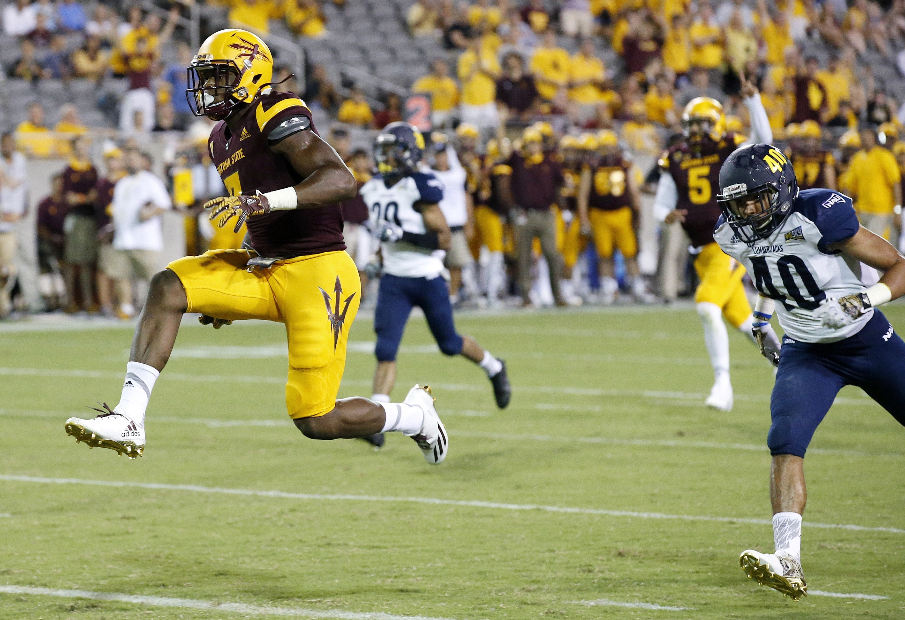 Arizona State's Kalen Ballage, left, jumps into the end zone for a touchdown as he gets past Northern Arizona's Keith Graham (40) and Maurice Davison, second from left, during the second half of an NCAA college football game Saturday, Sept. 3, 2016, in Te