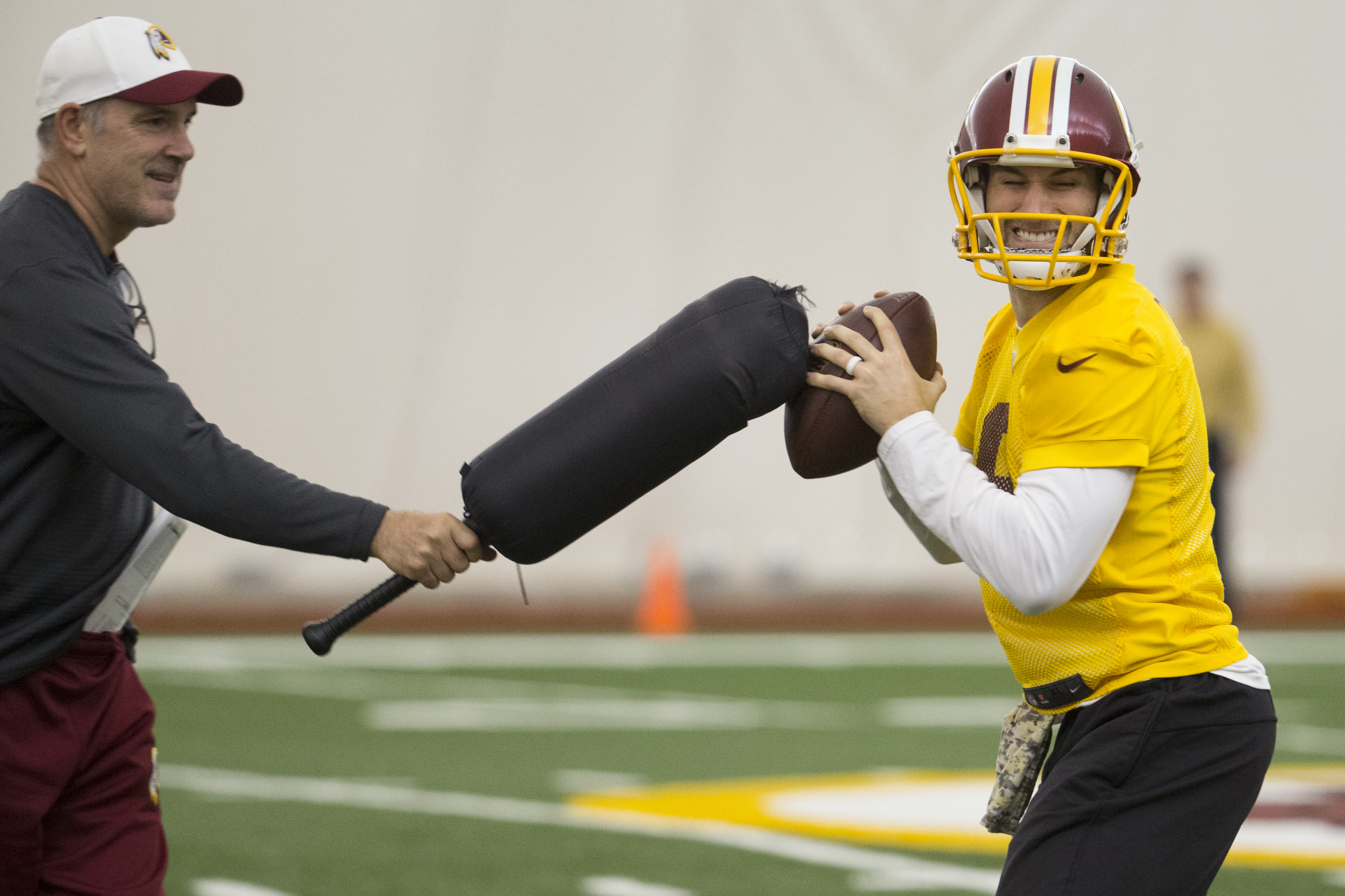 FILE - In this Friday, Jan. 8, 2016, file photo, Washington Redskins quarterback Kirk Cousins, right, works with quarterbacks coach Matt Cavanaugh on a ball protection drill during practice at the team's NFL football training facility at Redskins Park, in